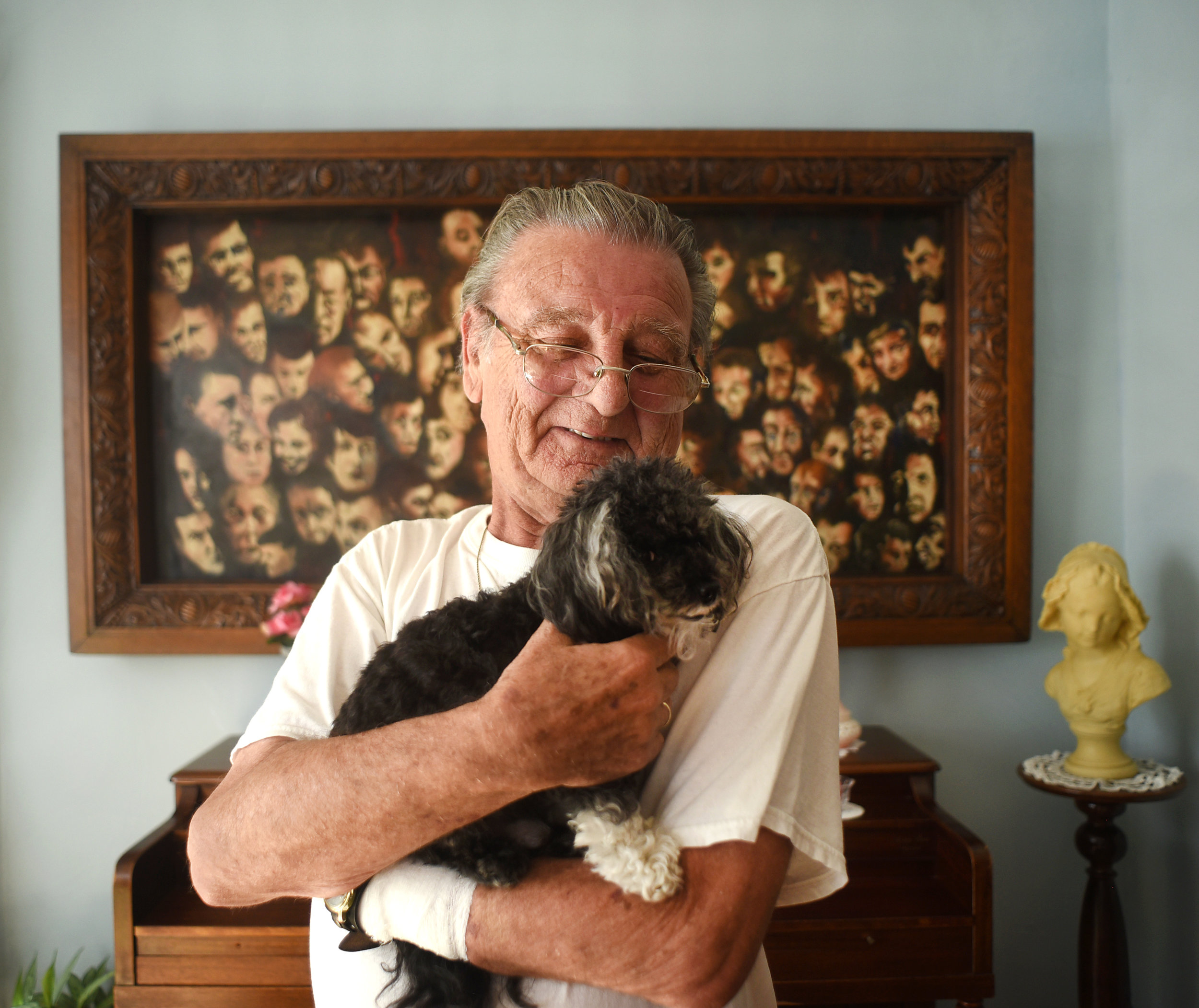 """Robert Verdonck, a Flemish painter,holds his dog, Tobias, a nine-year-old teacup poodle and shihtzu mix, in front of one of his paintings in his home July 7, 2016. """"When I'm painting,"""" Verdonck said, """"I feel like I'm in my own kind of world."""""""