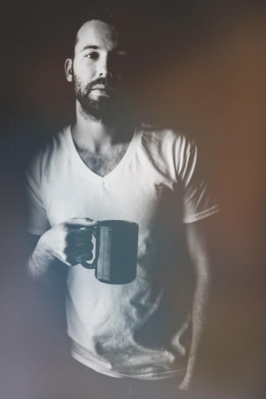 Daniel Alkato holding a coffee mug black and white