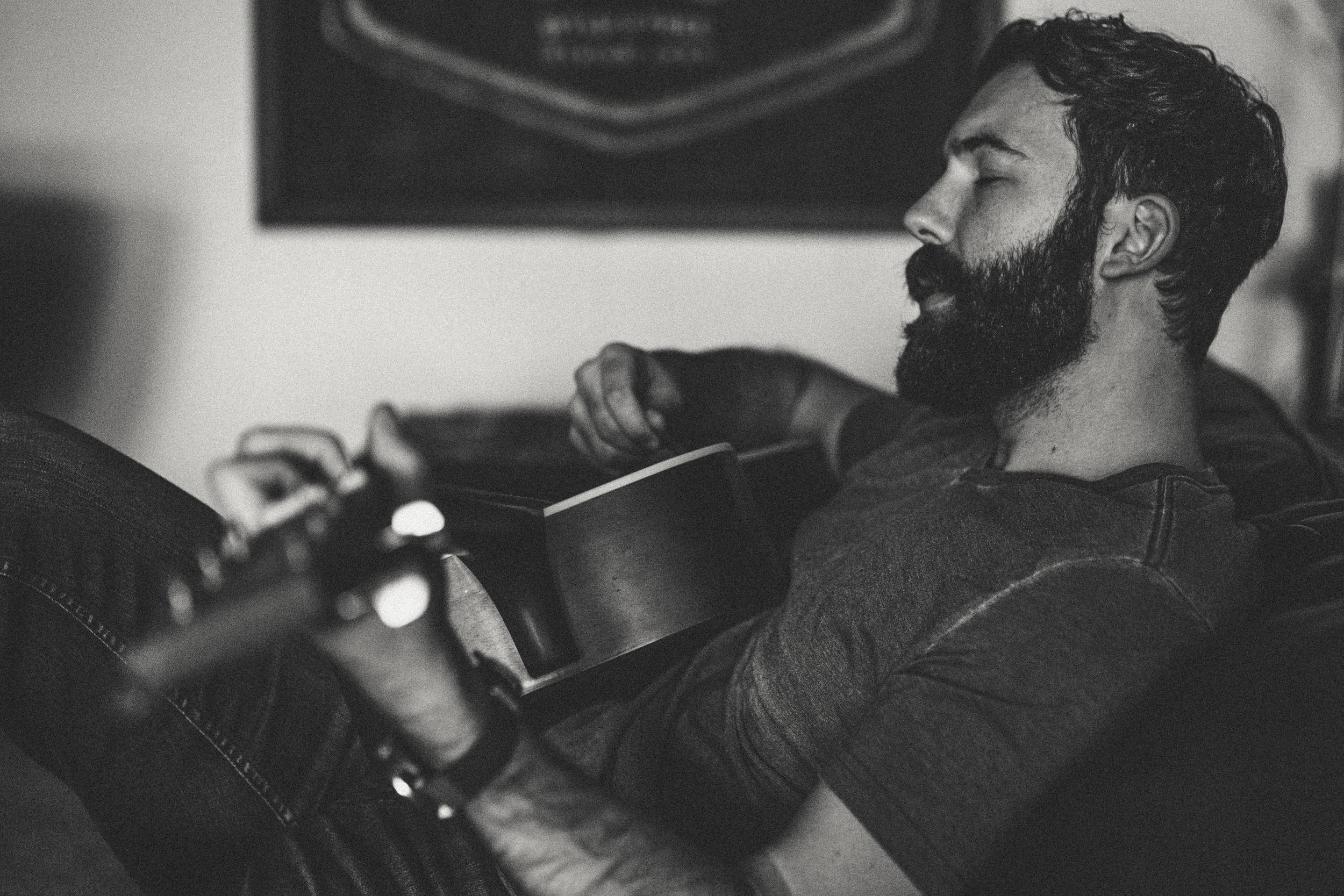 Daniel Alkato Playing Acoustic Guitar beard Black and White