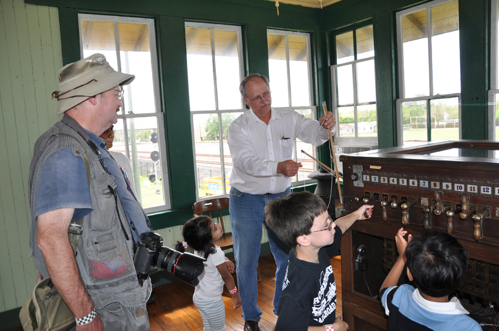Jim Vollmer describes to museum visitors some of the duties of the Towerman and shows the original equipment they used in Tower 17.