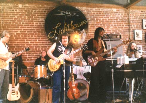 "Band #2 – 1984    Here we are playing at the famous club, ""The Lighthouse"" in Hermosa Beach, CA. John Woodhead, Jon Hurley, myself, Calvin Hardy, Wayne Sharp and drummer (not seen) Jan Ashley.."