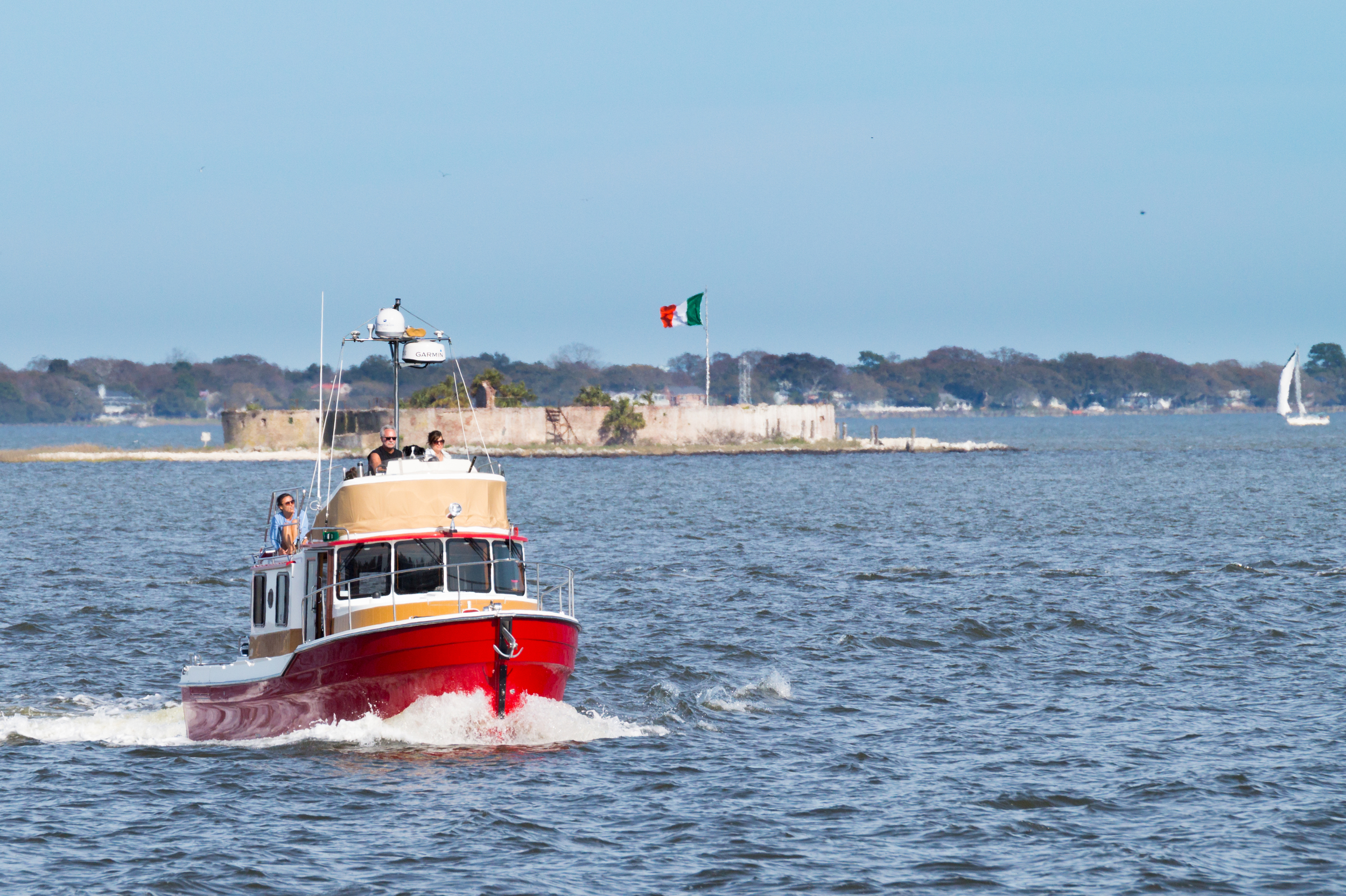 A boat crossing in front of Castle Pinckney during a sunny day.