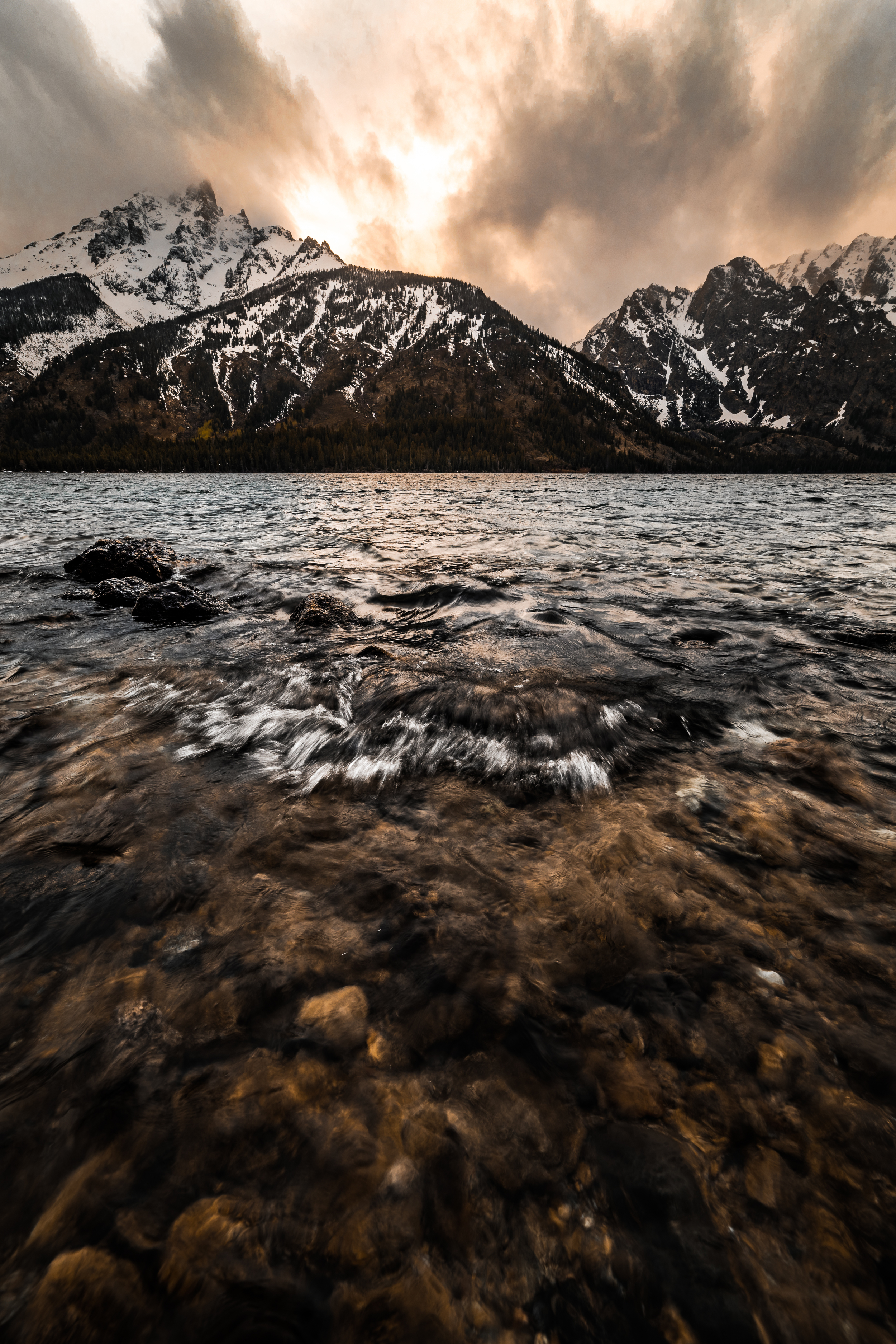 Sunset behind the Tetons at Jenny Lake creating glowing clouds in 'Glowing Tetons""