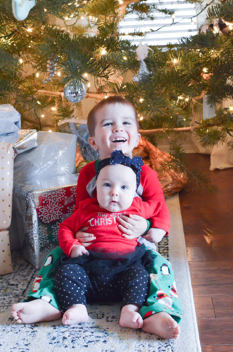 Babies sitting in front of Christmas tree | Holiday traditions to start with your family