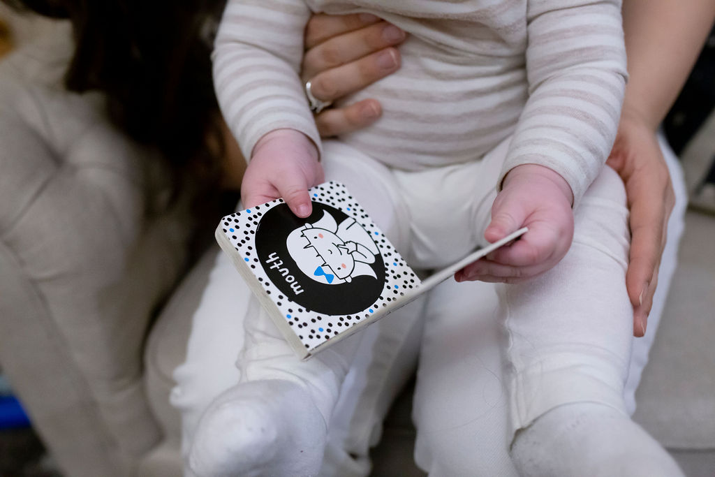 baby reading black and white book | Momma Society
