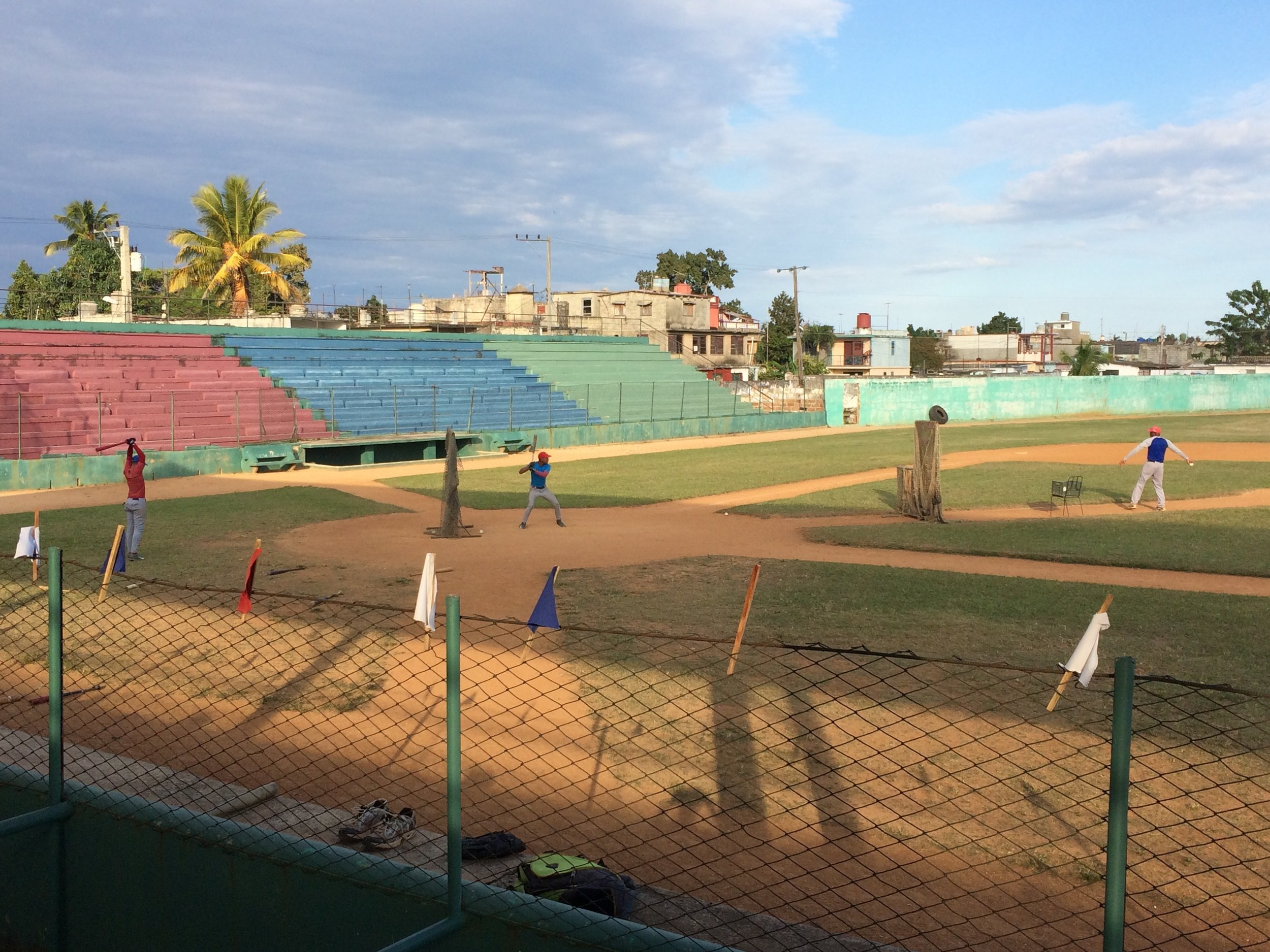 A very old baseball stadium, with young players at practice