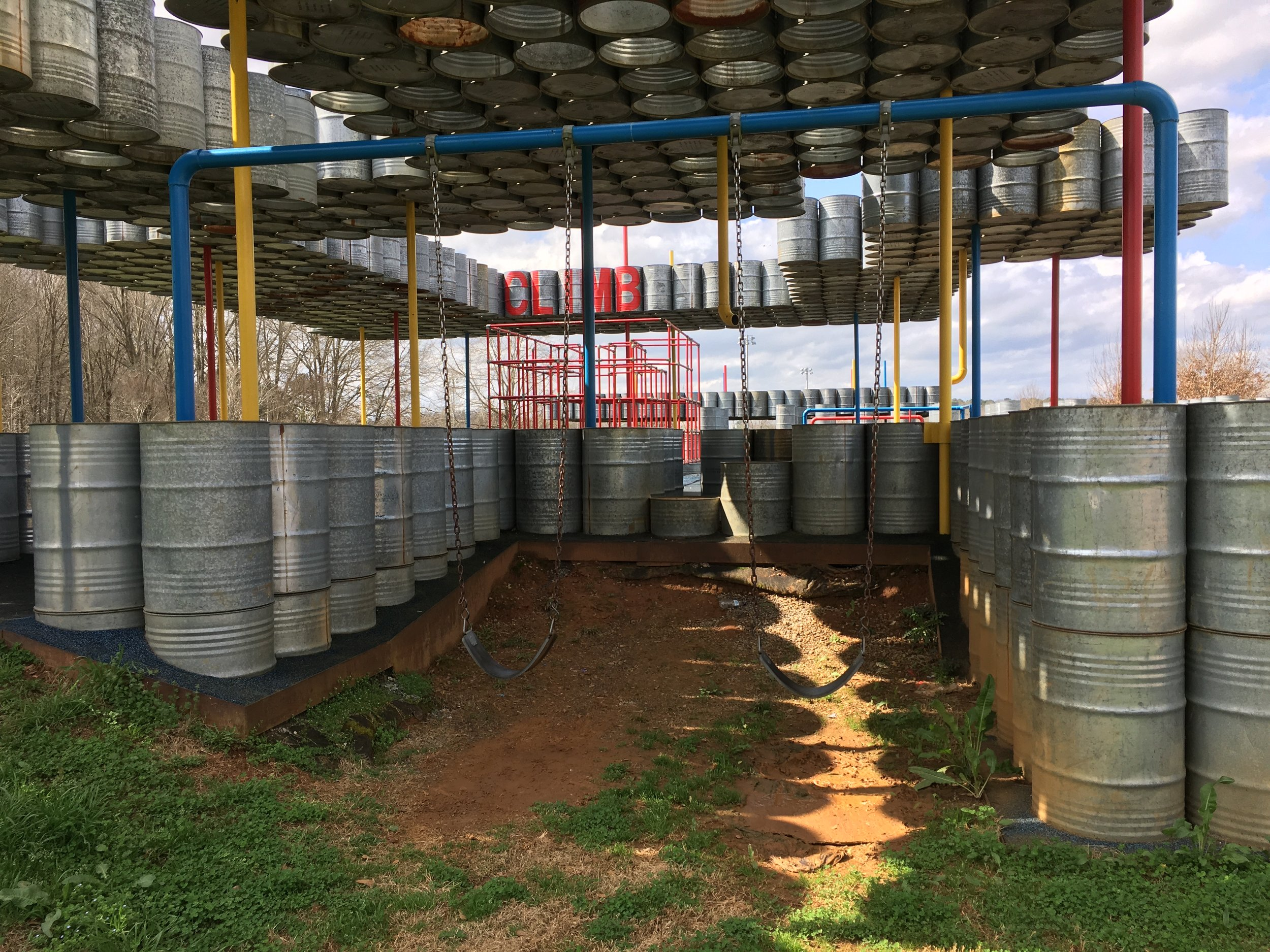 Lions Park playscape created from metal barrels given to Rural Studio by a large company that would otherwise have paid to dispose of them in landfill. Students also used them to create a passive solar heat storage system for their greenhouse.