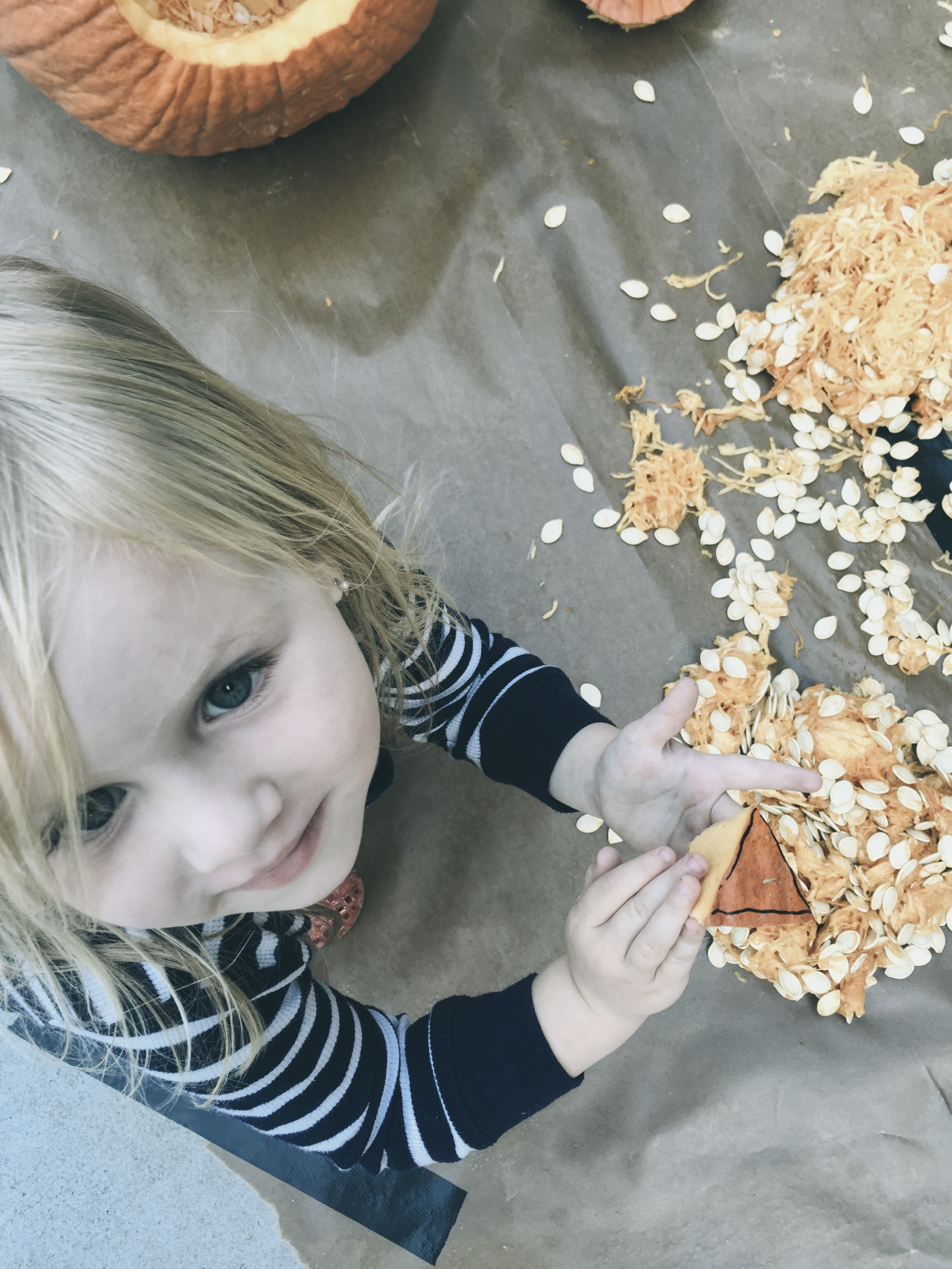 little girl carving a pumpkin