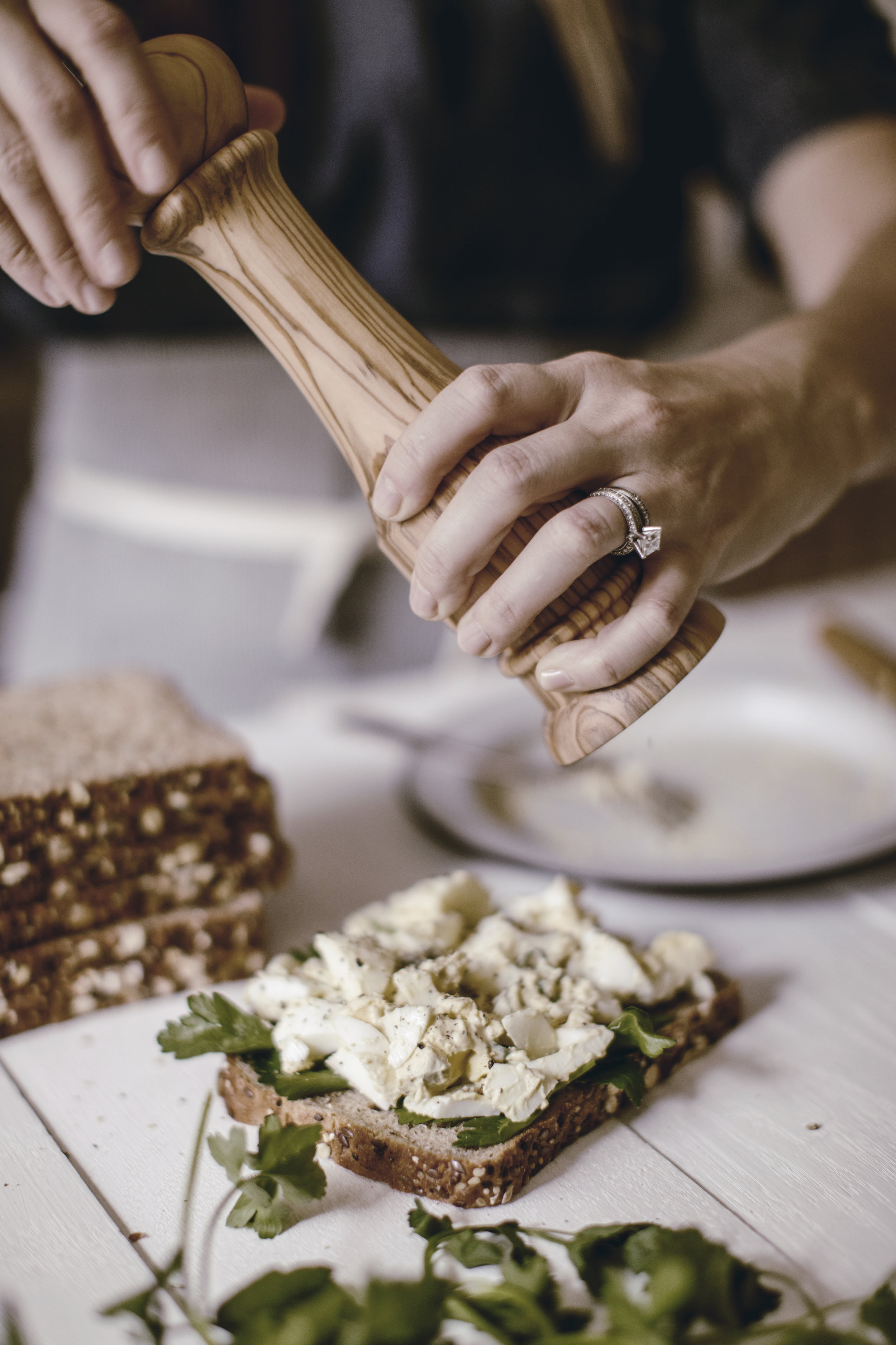seasoning a fresh egg salad sandwich / wooden pepper mill / heirloomed