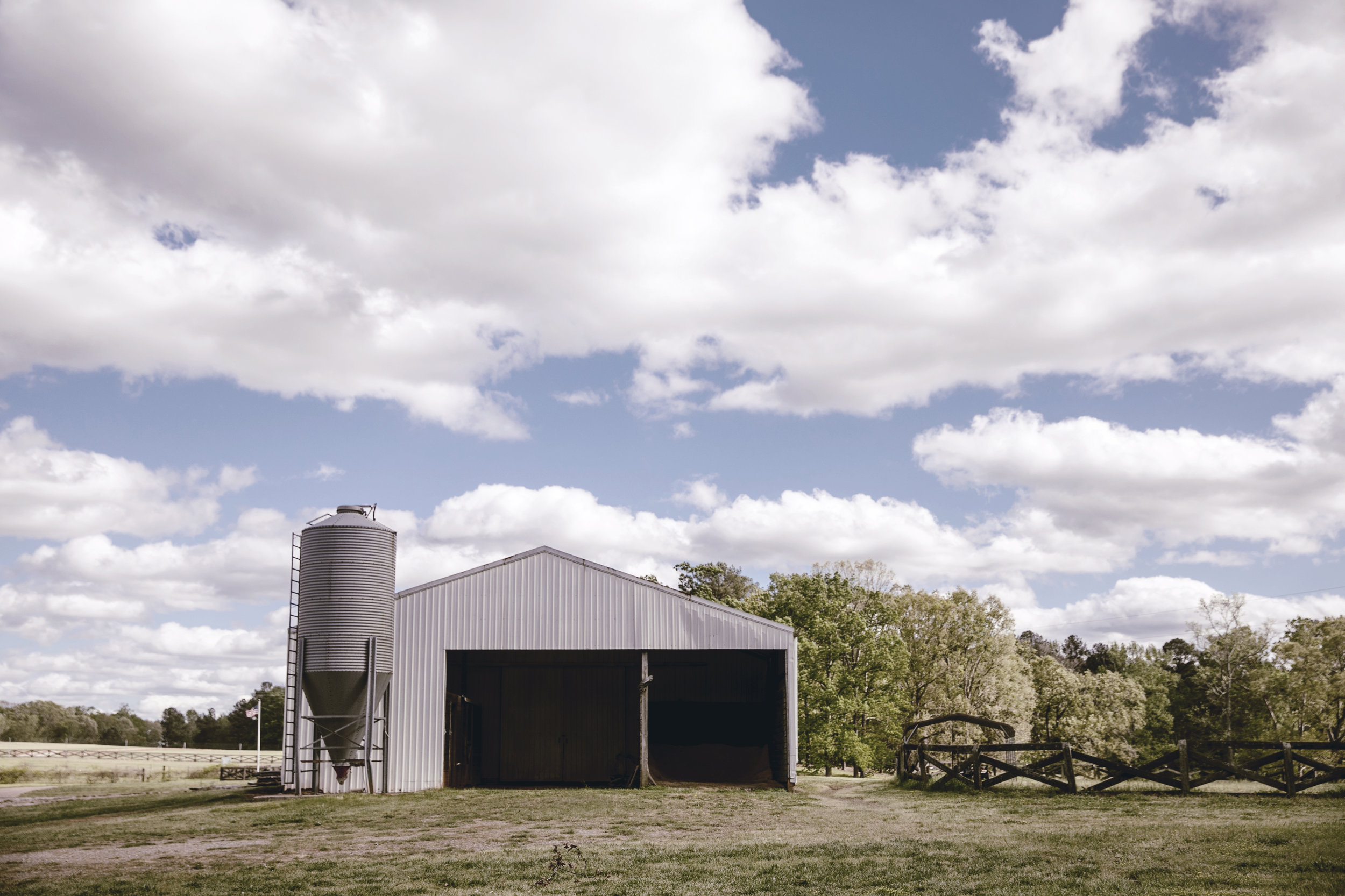 barn and silo with wooden cross buck fence at the farm / heirloomed