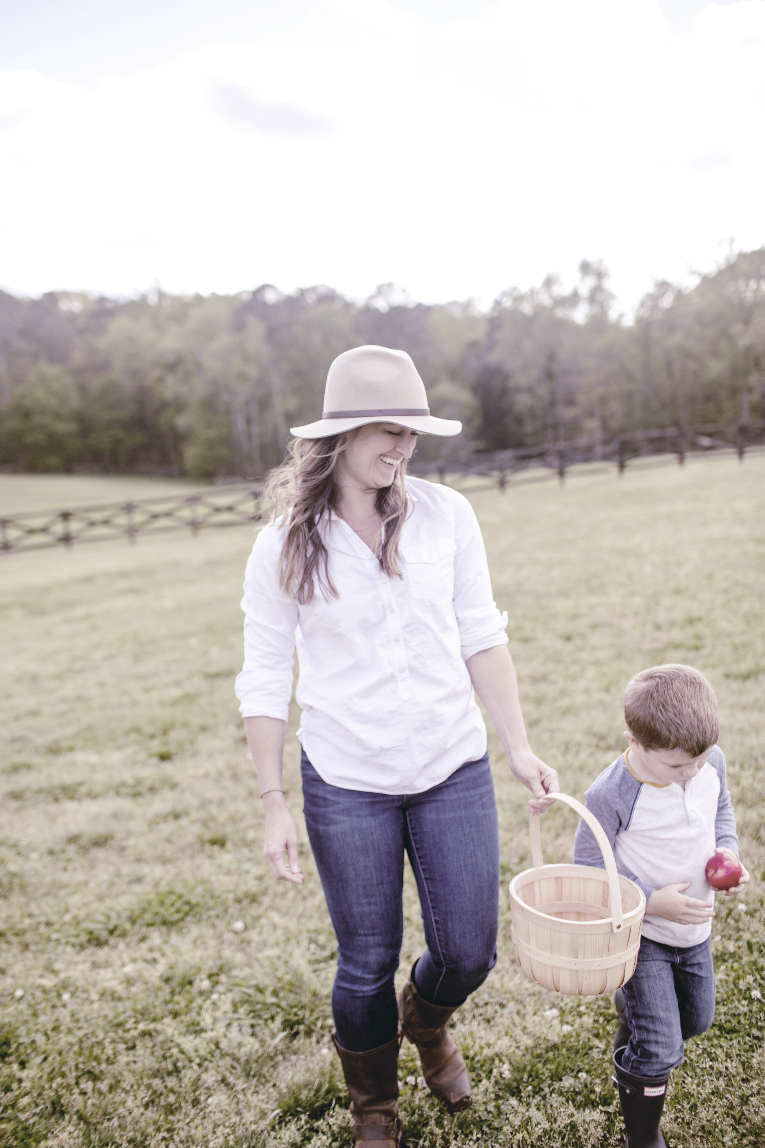 mom and son feeding animals at the farm / heirloomed