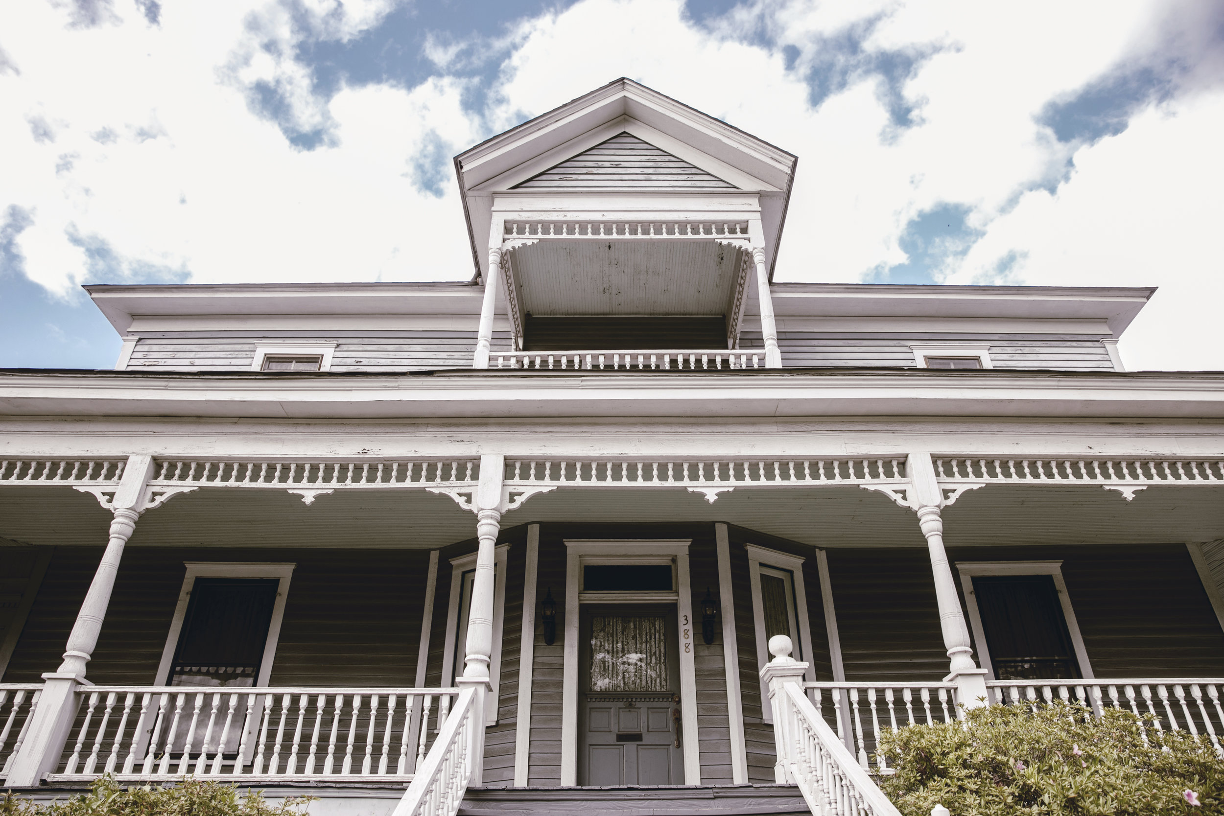 historic home with chipping paint front steps and southern front porch / heirloomed