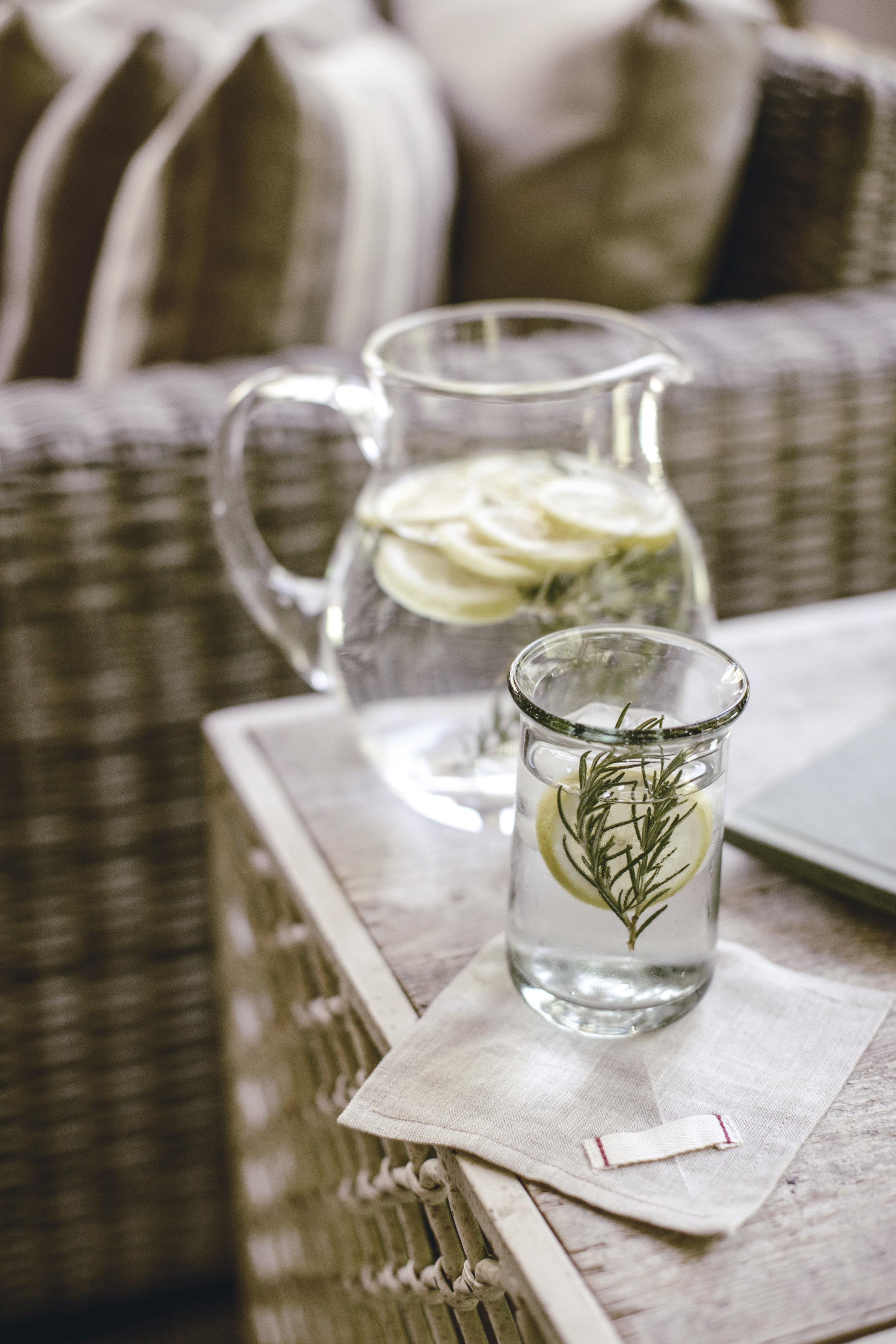 glass pitcher of lemon and rosemary flavored water / heirloomed