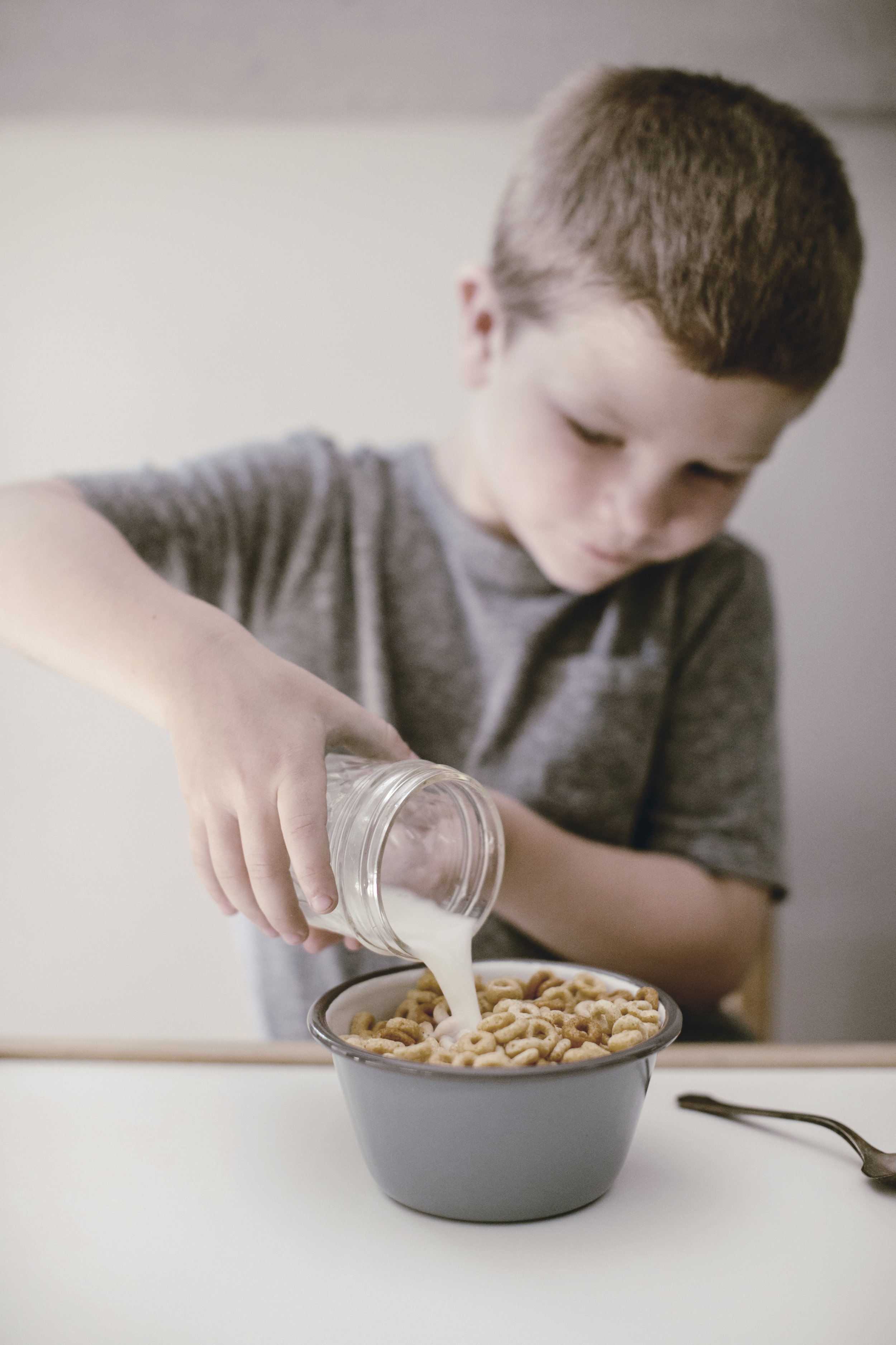 child pouring milk for cereal bowl of Cheerios / heirloomed