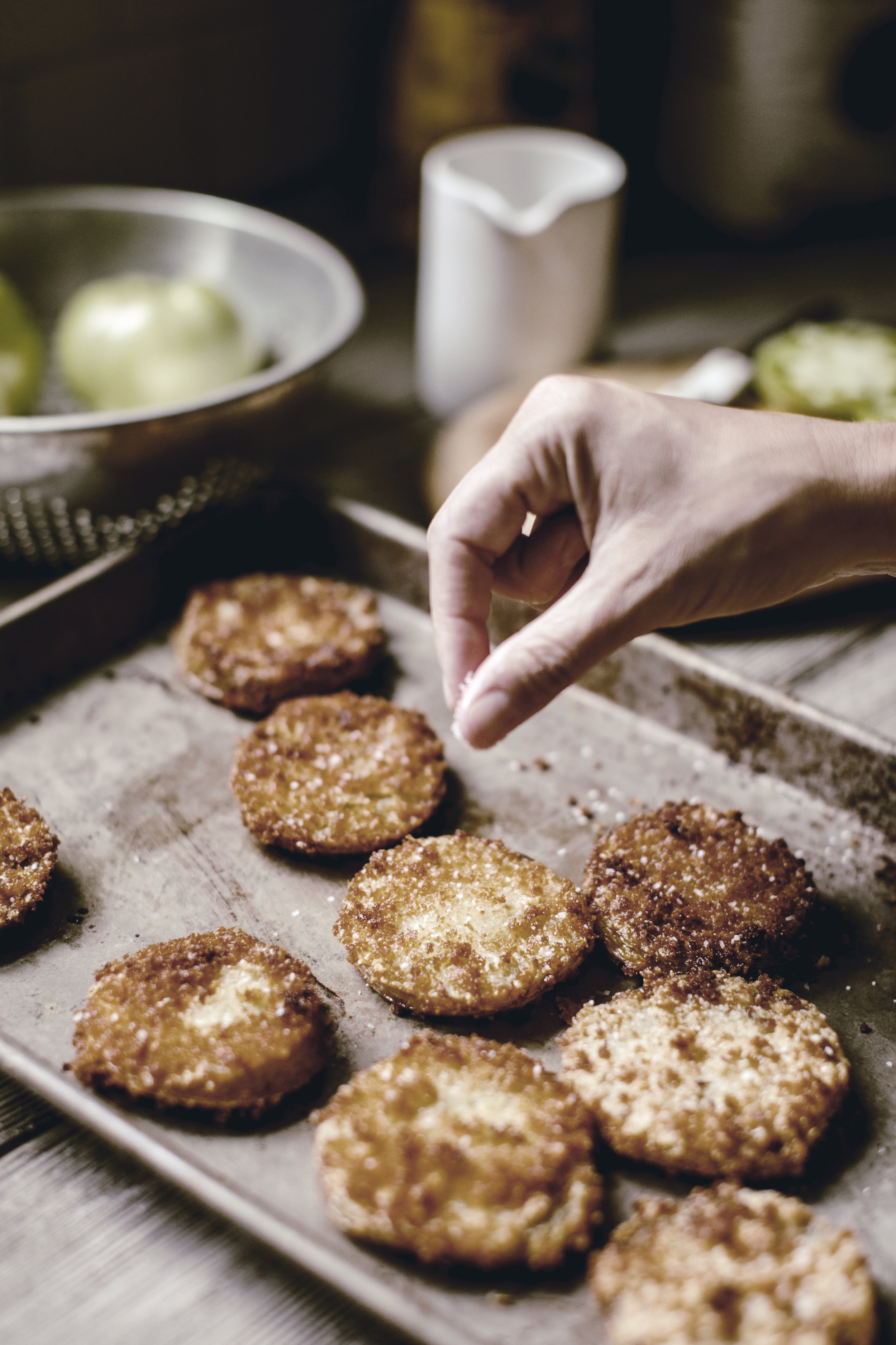 salting a pan of fried green tomatoes / heirloomed