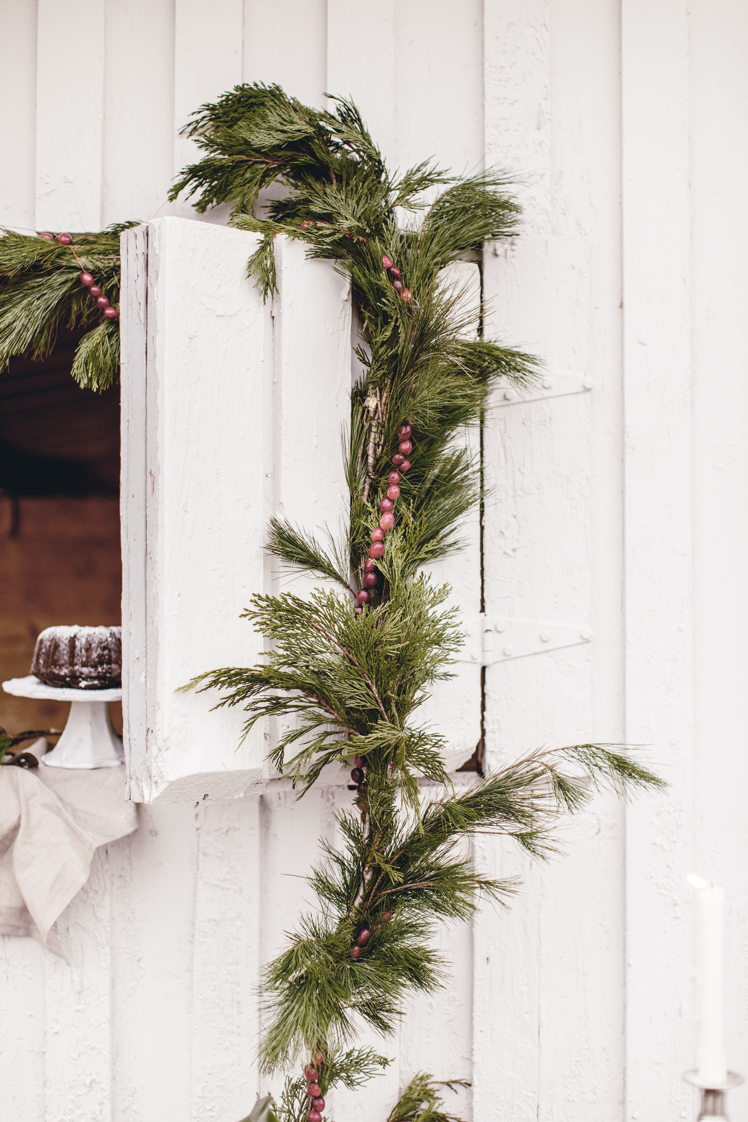 rustic barn with fresh greens and cranberry garland for holiday decorating / heirloomed