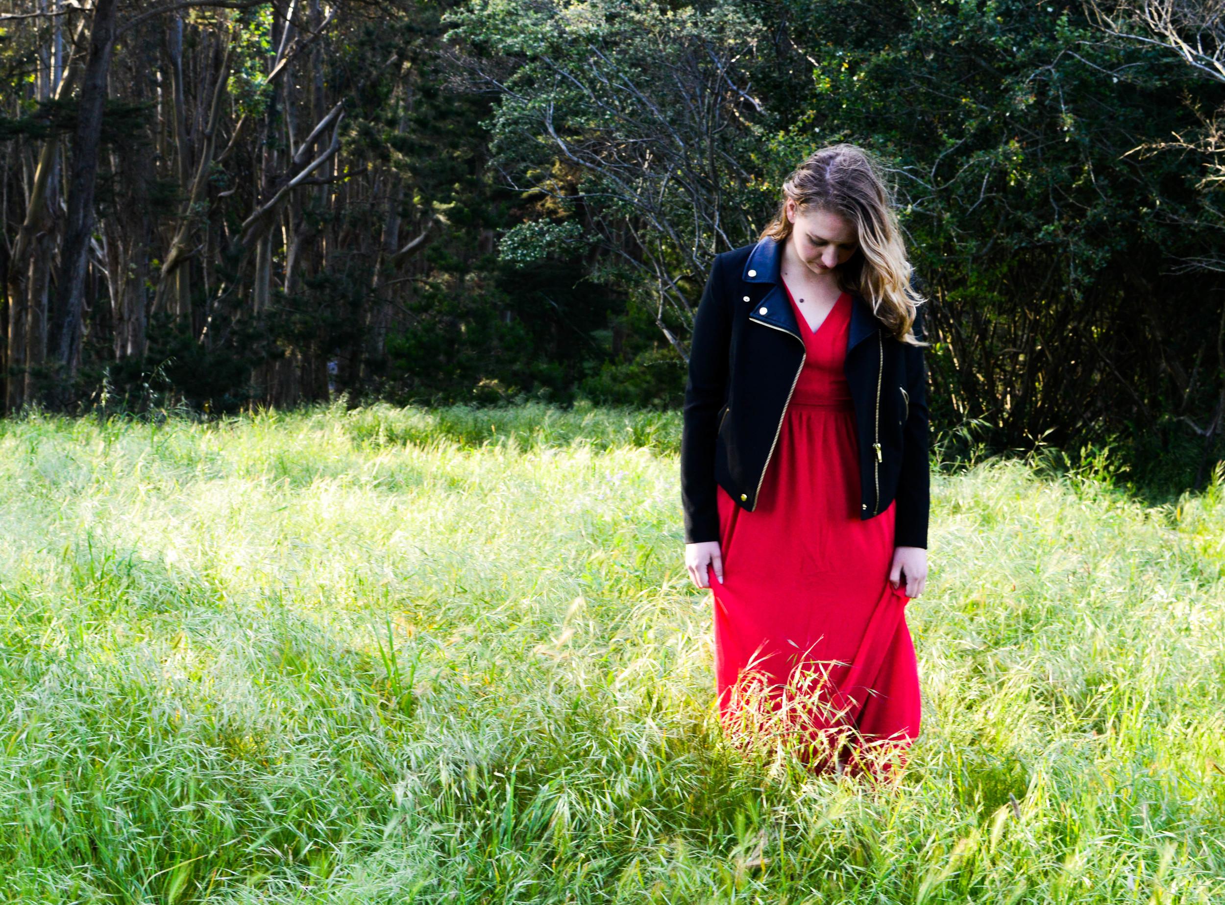 Girl in a red dress walking through field
