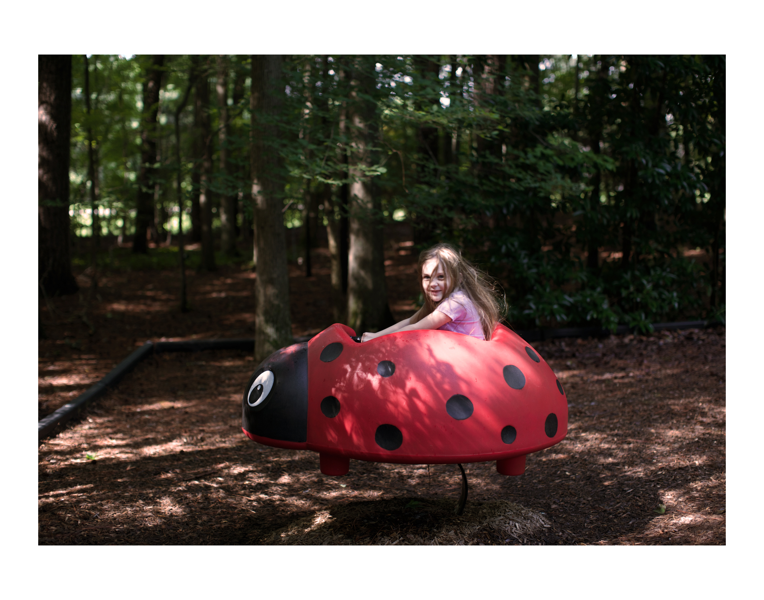 Karina riding the ladybug at Sandy Bottom Nature Park.