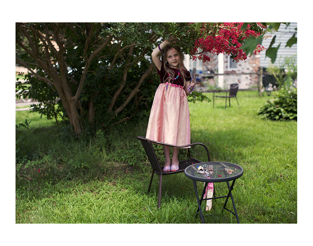 Karina playing dress up in her front garden.