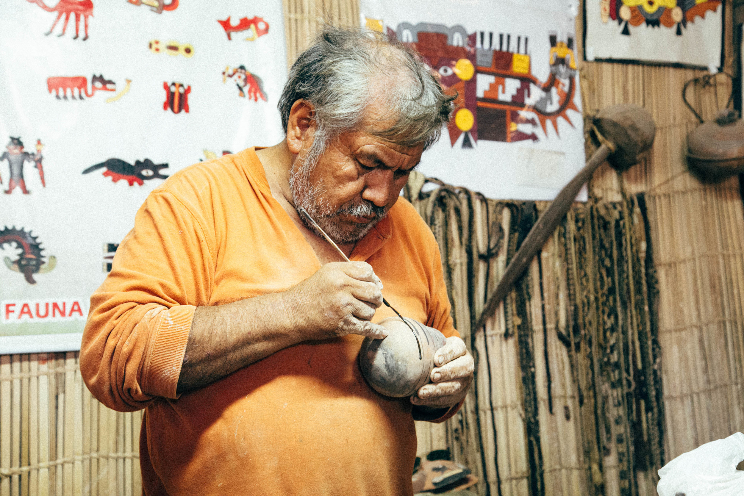 In this photo, he's showing us how he paints the designs on the pot.