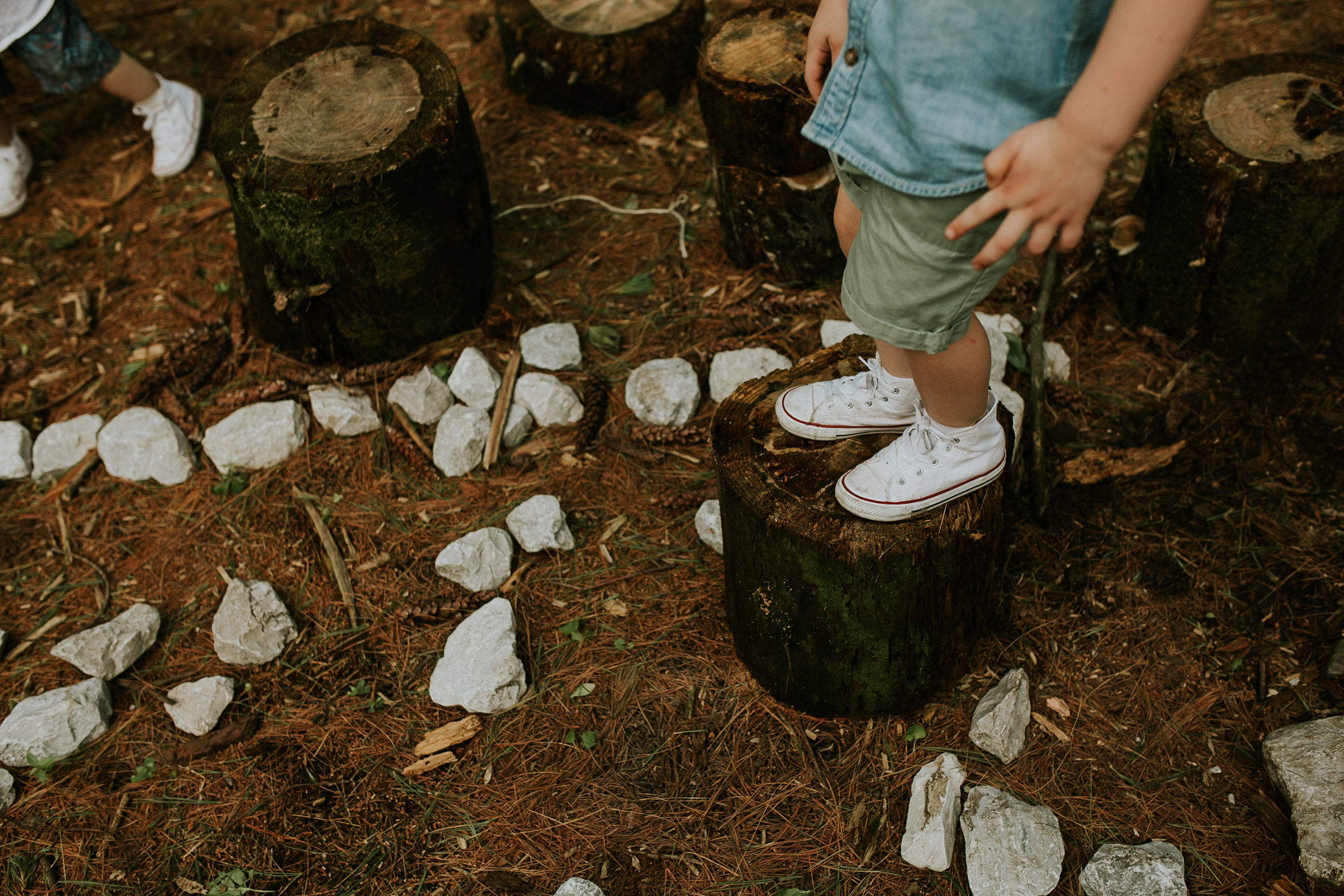 flynn-family-kid-converse-shoes-on-rocks-and-tree-trunks-jester-park-iowa-raelyn-ramey-photography.jpg