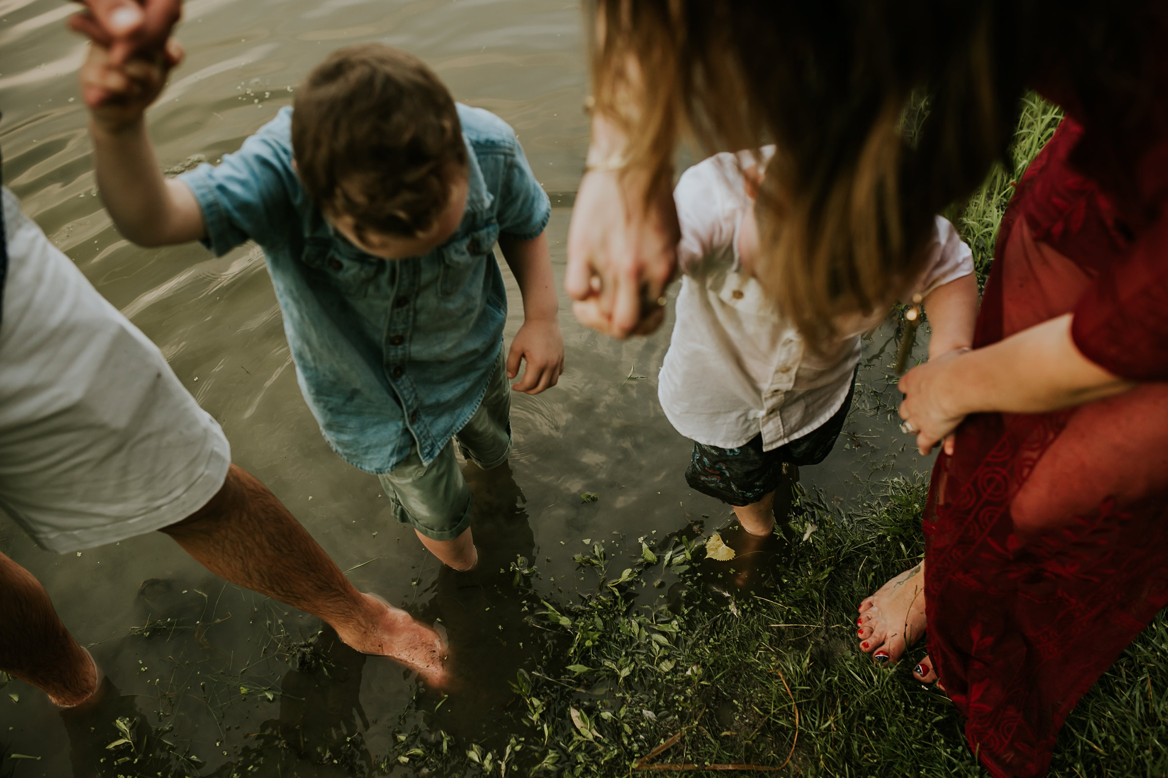 flynn-family-standing-in-lake-jester-park-iowa-raelyn-ramey-photography.jpg