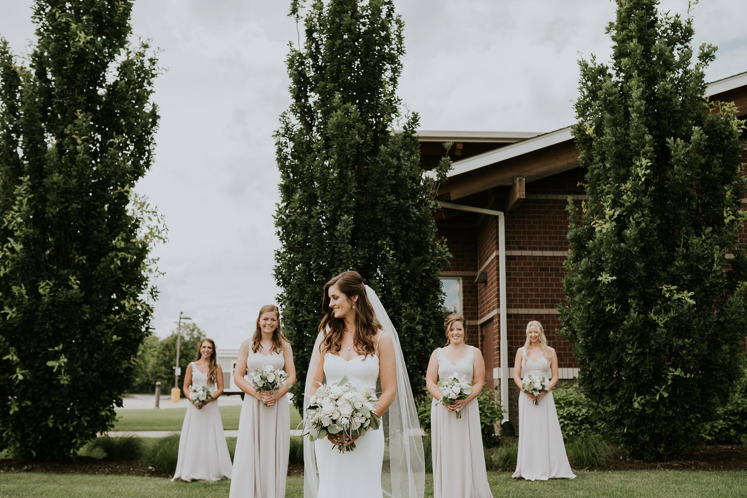 mr-mrs-hull-bride-posing-with-bridesmaid-in-v-shape-desmoines-iowa-raelyn-ramey-photography-231.jpg