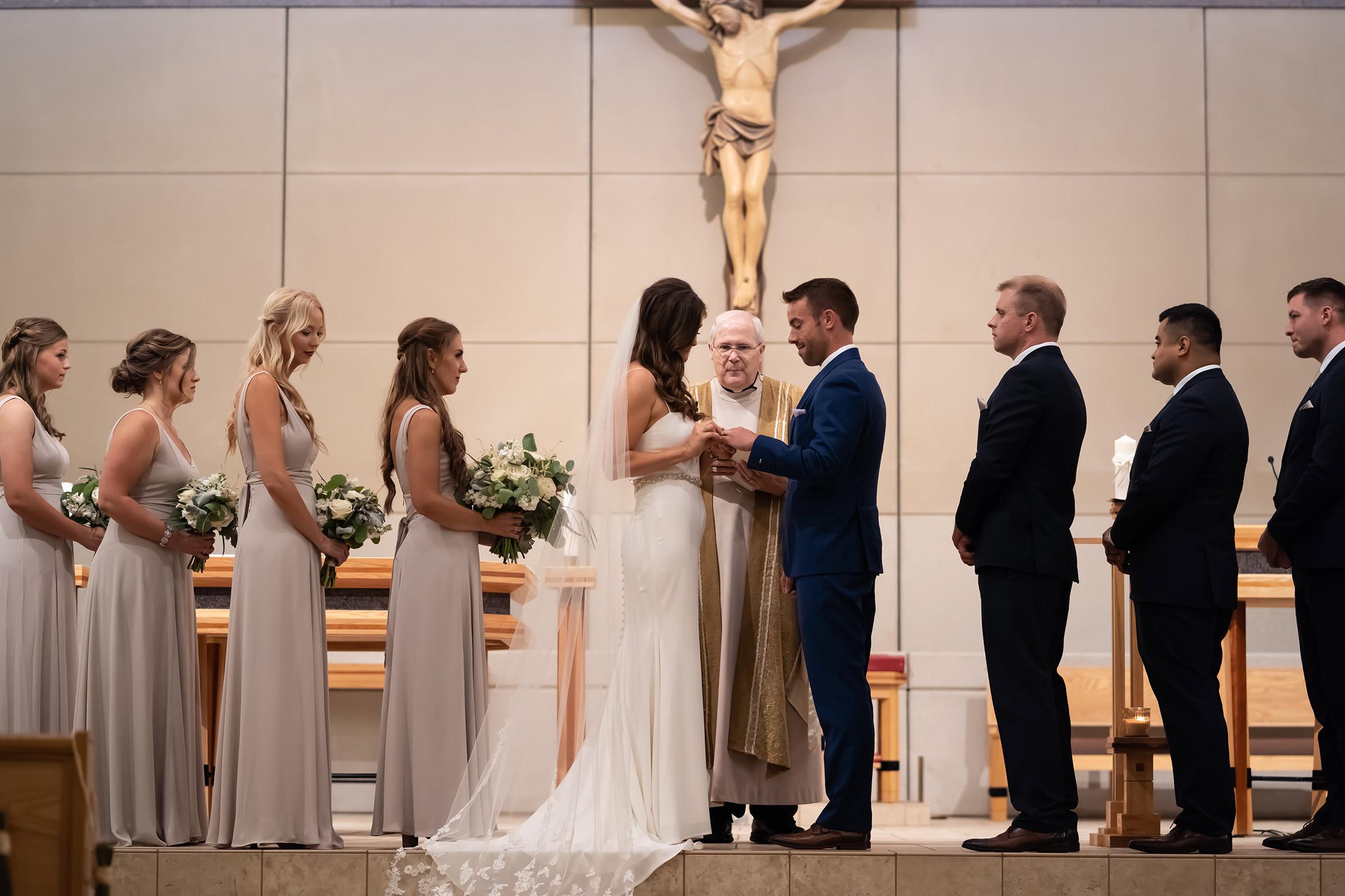 mr-mrs-hull-bride-putting-ring-on-groom-ceremony-st-boniface-church-waukee-desmoines-iowa-raelyn-ramey-photography-335.jpg