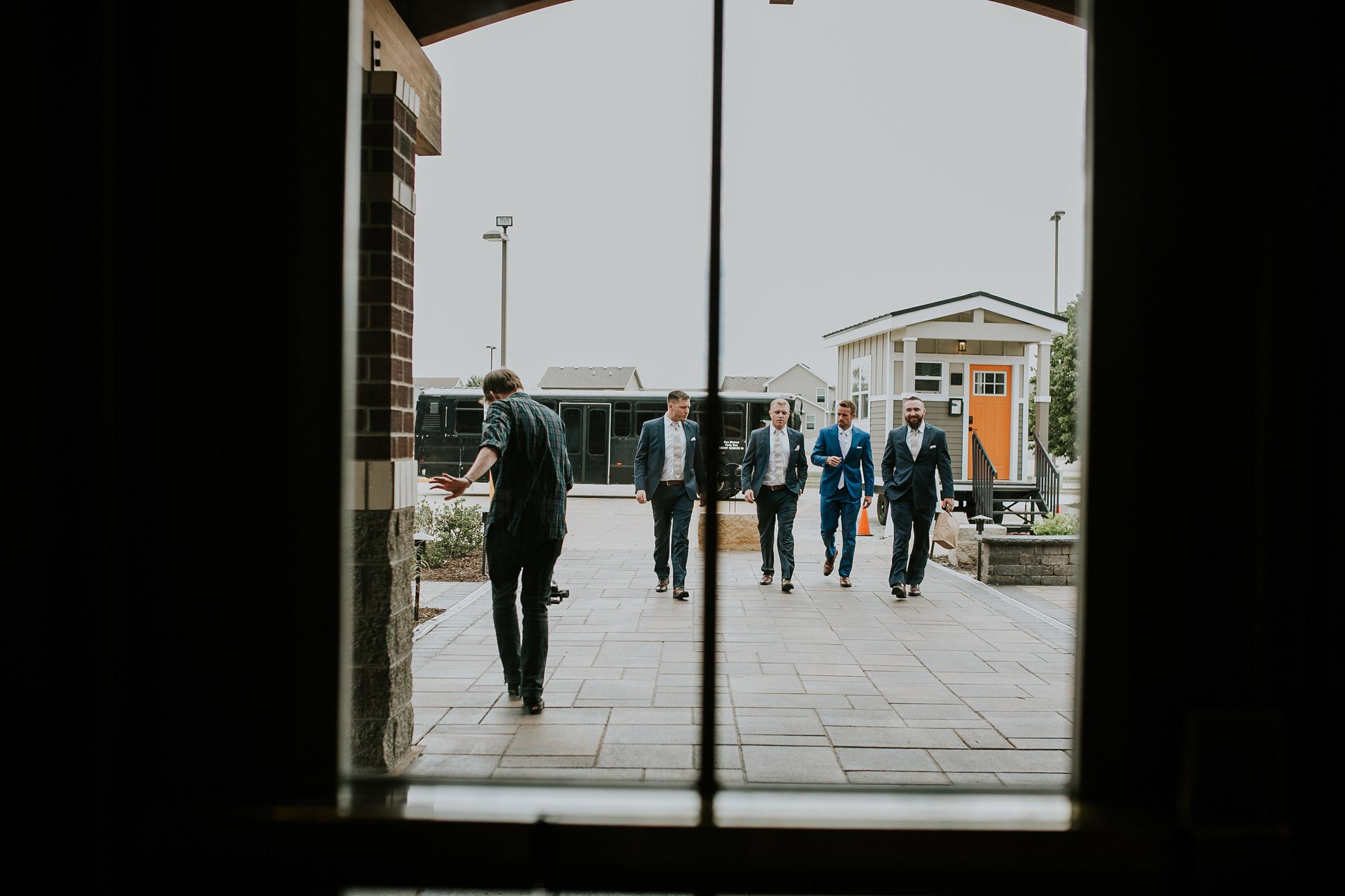 mr-mrs-hull-groom-walking-into-st-boniface-church-waukee-desmoines-iowa-raelyn-ramey-photography-164.jpg