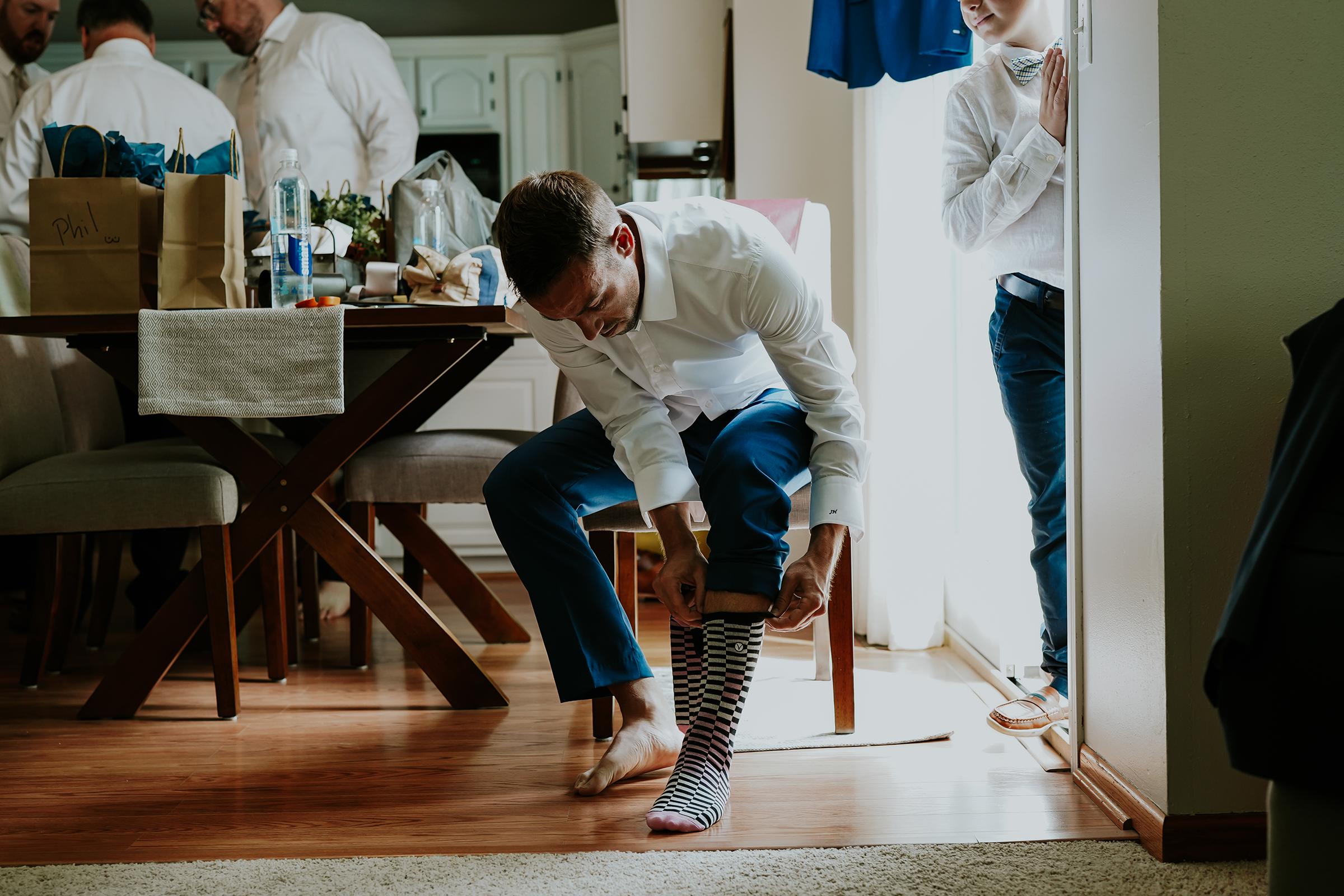 mr-mrs-hull-groom-putting-socks-on-desmoines-iowa-raelyn-ramey-photography-107.png