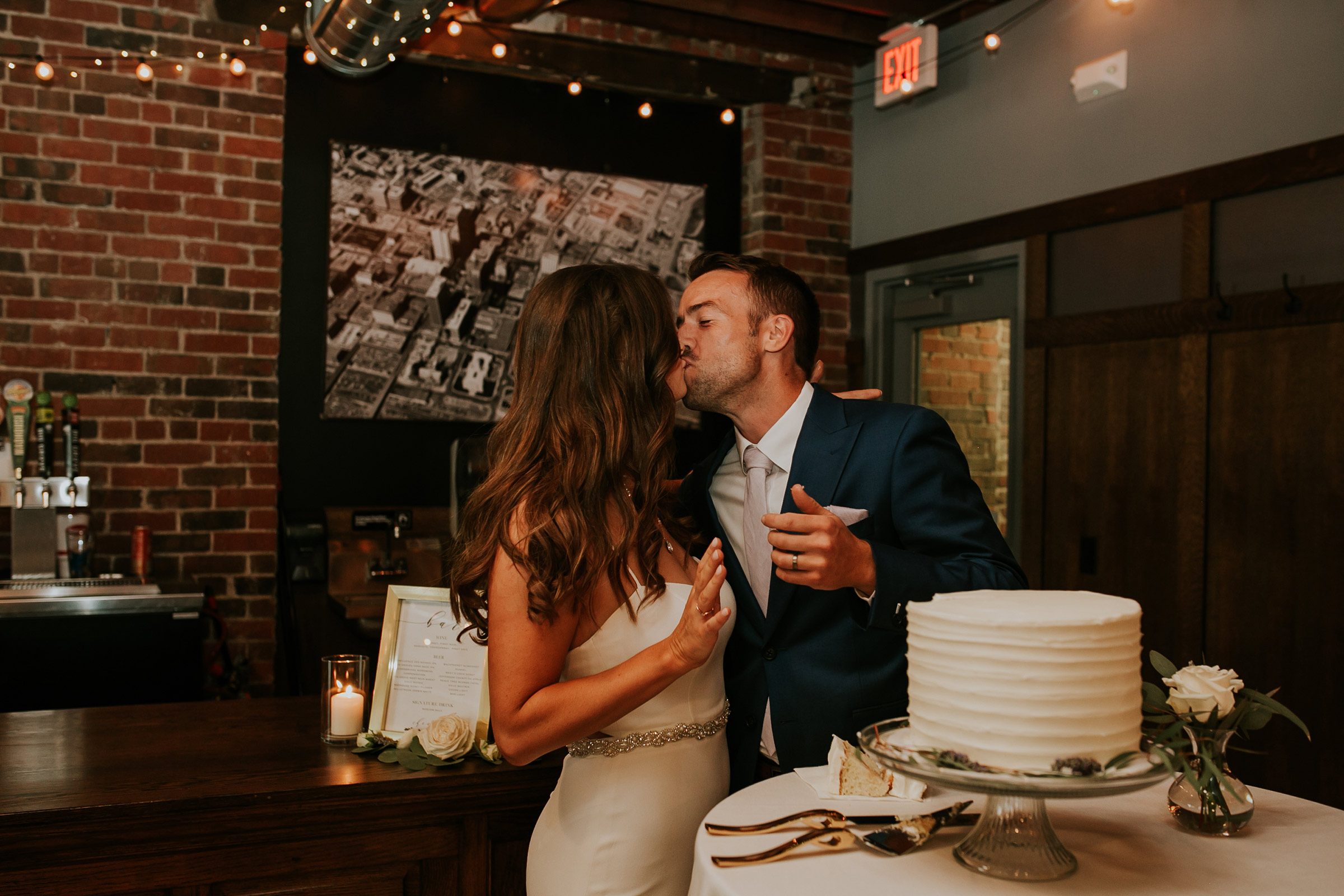 mr-mrs-hull-couple-kissing-cake-cutting-taproom-desmoines-iowa-raelyn-ramey-photography-554.jpg
