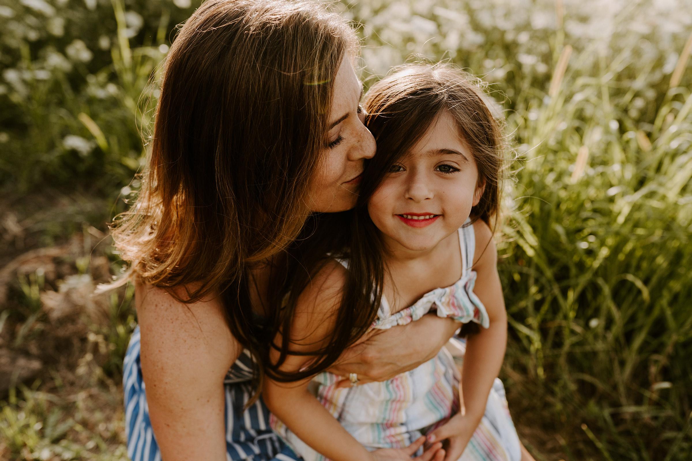 natale-family-mom-hugging-daughter-while-smiling-iris-aisle--winterset-iowa-raelyn-ramey-photography-29.jpg