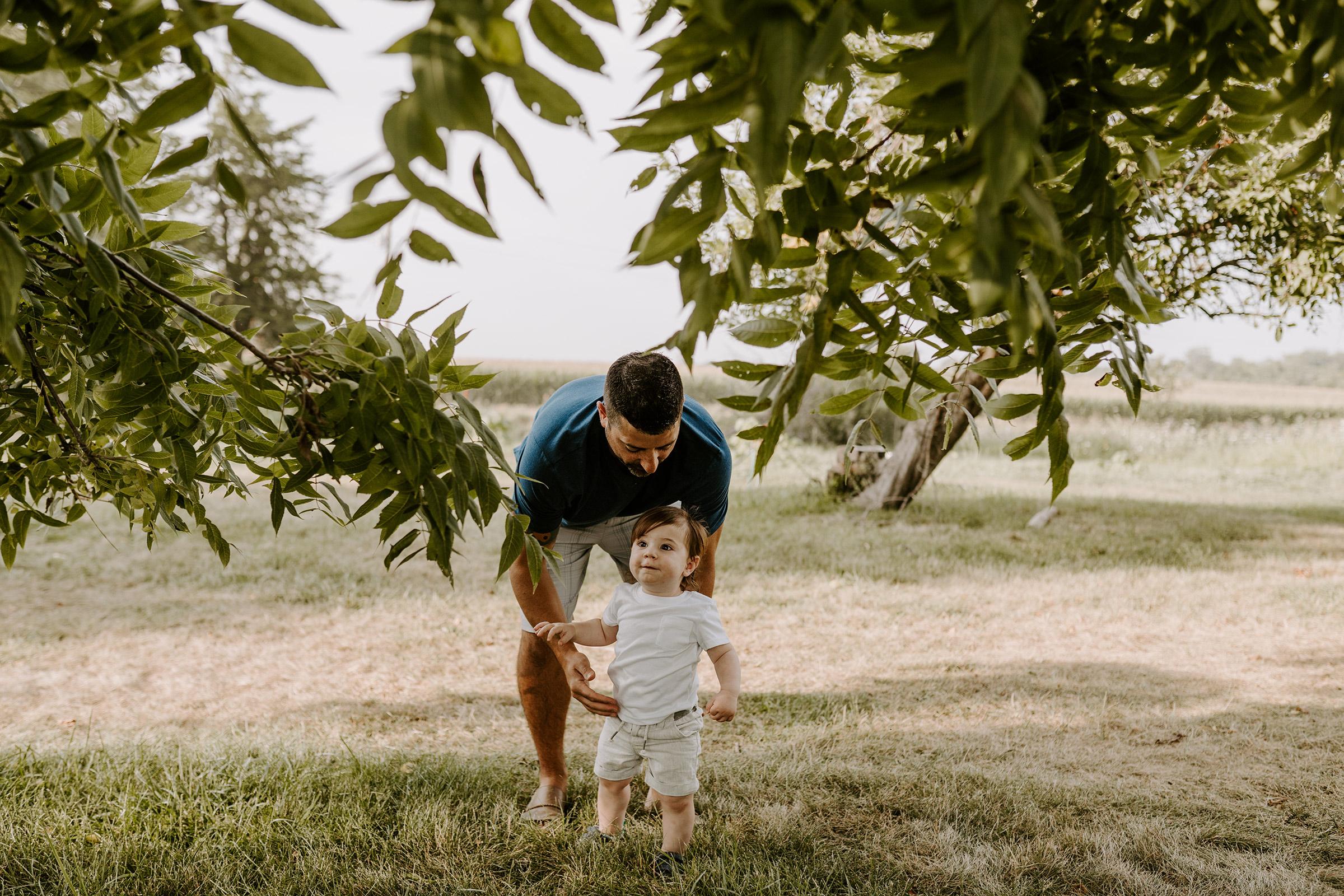 natale-family-son-walking-with-dad-by-walnut-tree-iris-aisle--winterset-iowa-raelyn-ramey-photography-9.jpg