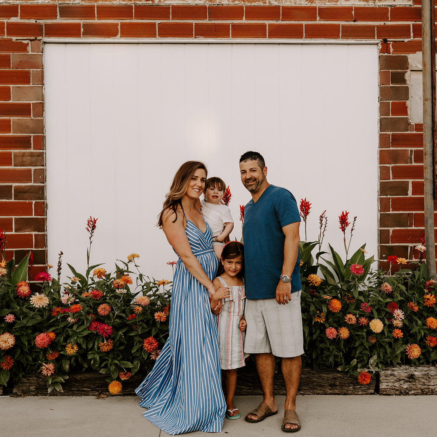 natale-family-standing-in-front-of-flowers-at-frostees-winterset-iowa-raelyn-ramey-photography-179.jpg