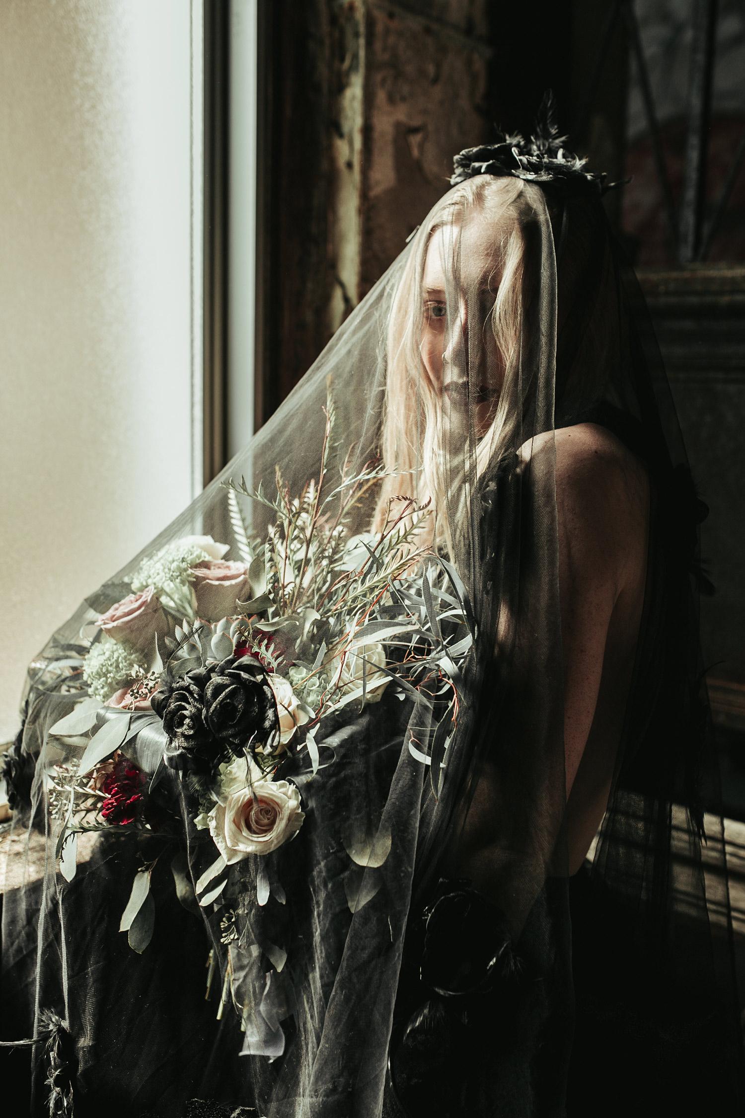 bride-holding-flowers-under-black-veil-black-dress-burlington-iowa-gothic-wedding-elopement-raelyn-ramey-photography-113.jpg