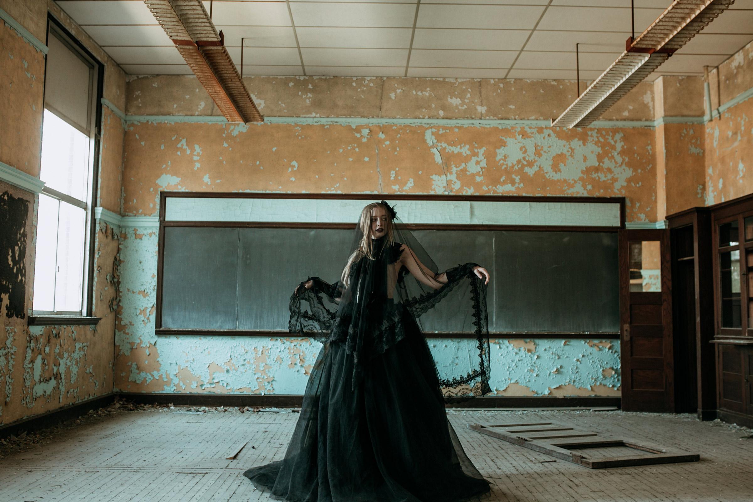 bride-standing-in-abandon-school-black-dress-and-viel-burlington-iowa-gothic-wedding-elopement-raelyn-ramey-photography-217.jpg