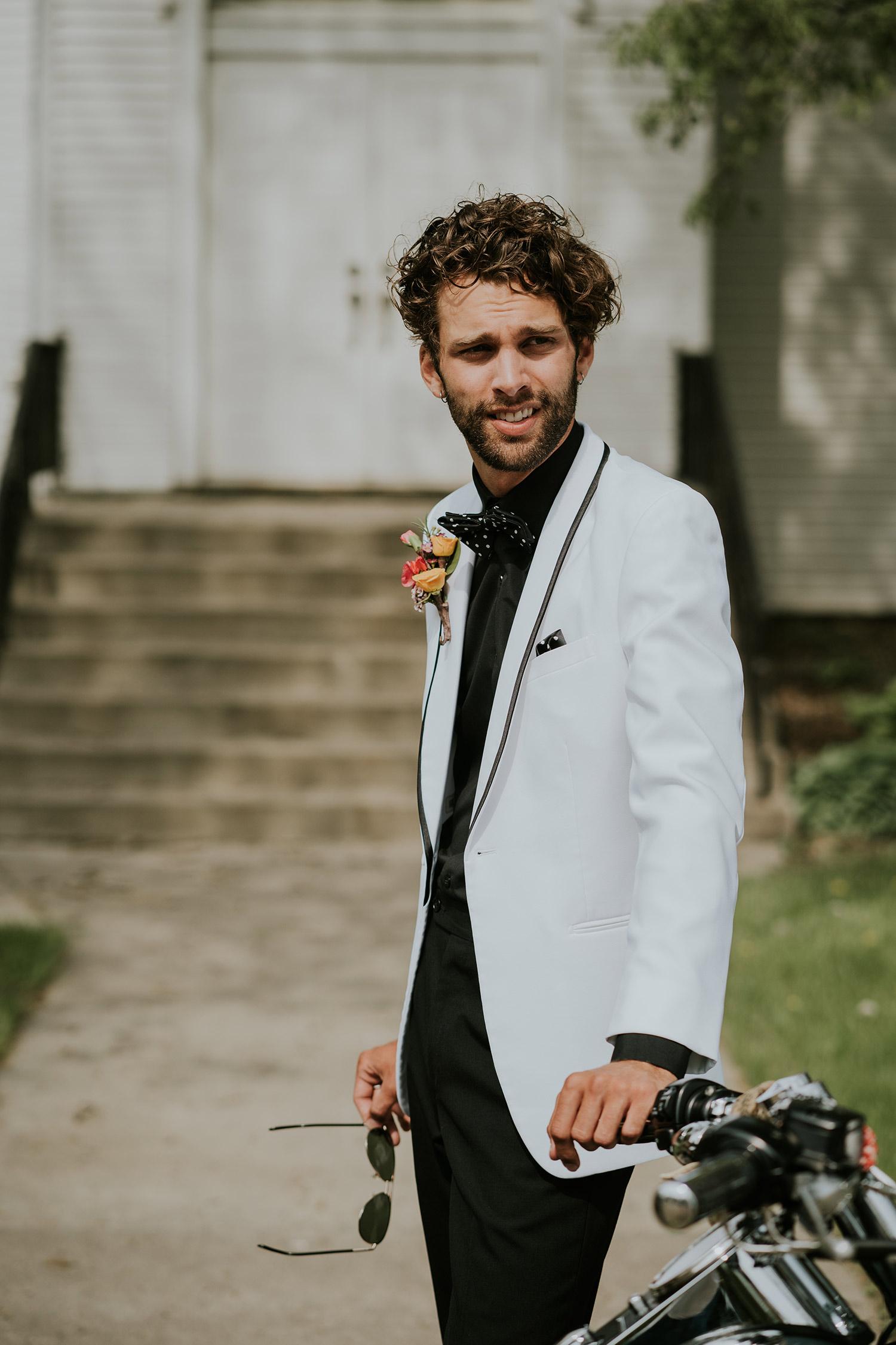 groom-standing-next-to-harley-at-ashton-chapel-iowa-road-trip-romance-wedding-raelyn-ramey-photography-18.jpg