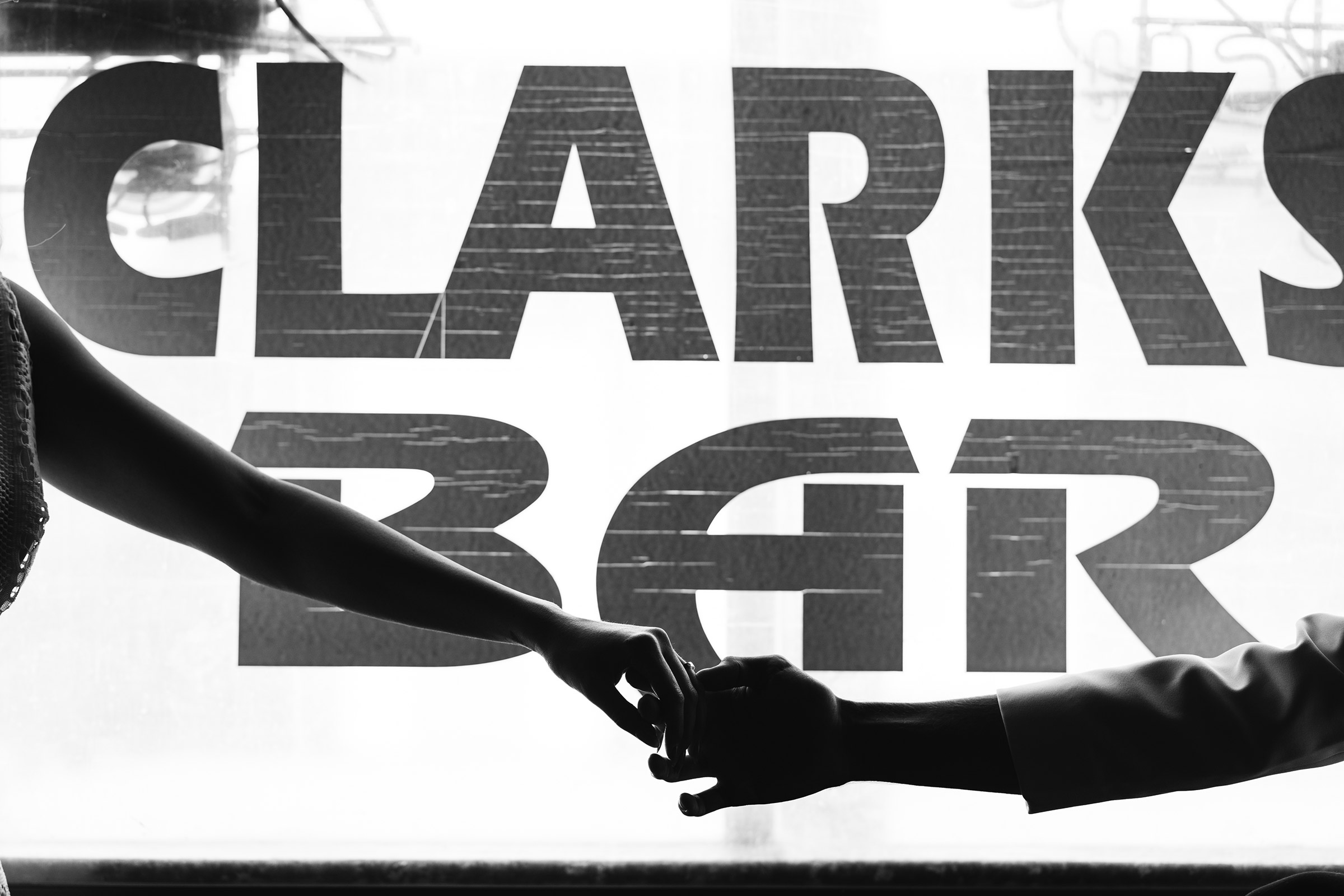 hands-with-rings-in-front-of-clarks-bar-window-iowa-road-trip-romance-wedding-raelyn-ramey-photography-69.jpg