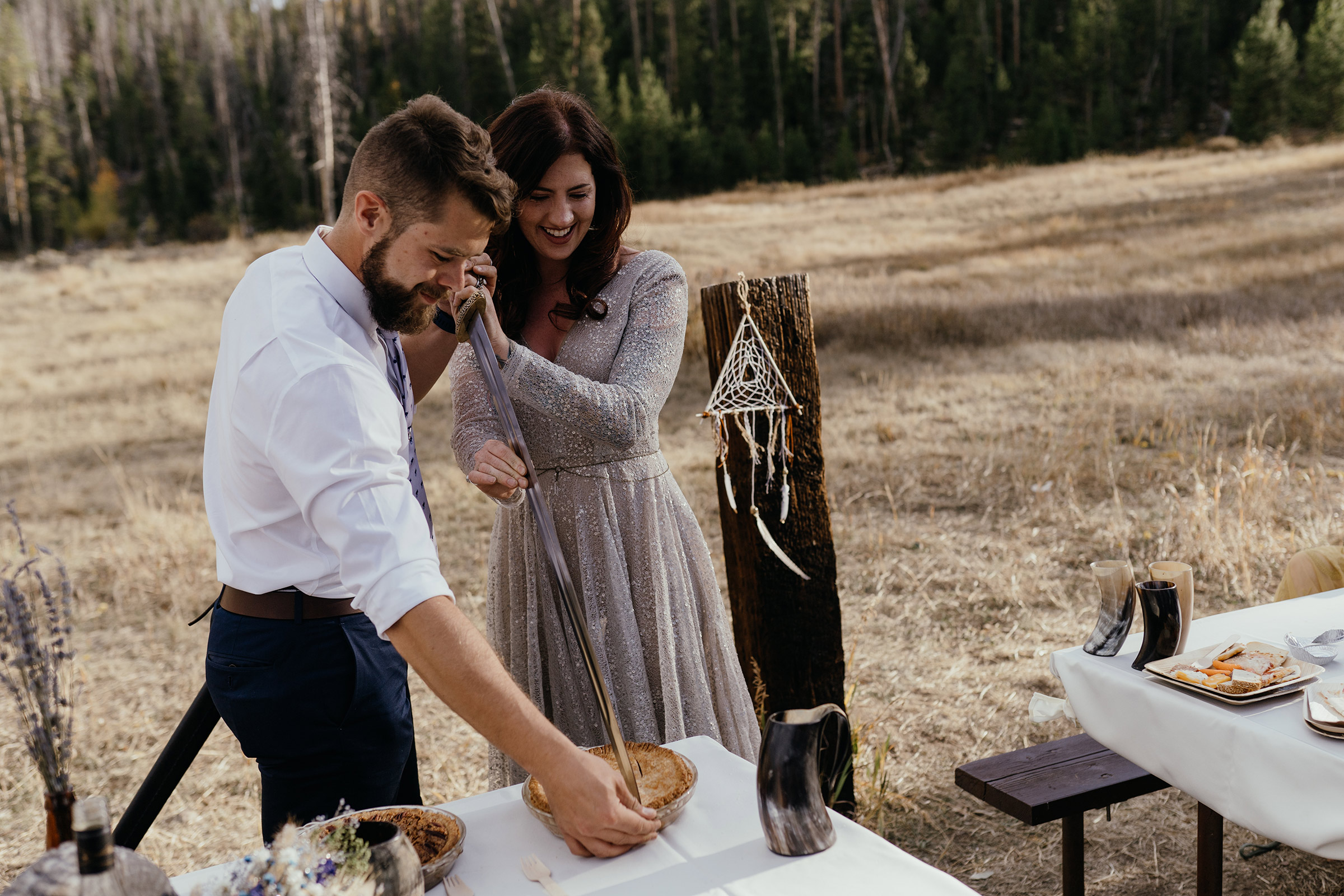 bride-and-groom-cutting-pie-with-a-sword-double-a-barn-grand-lake-colorado-raelyn-ramey-photography-612.jpg