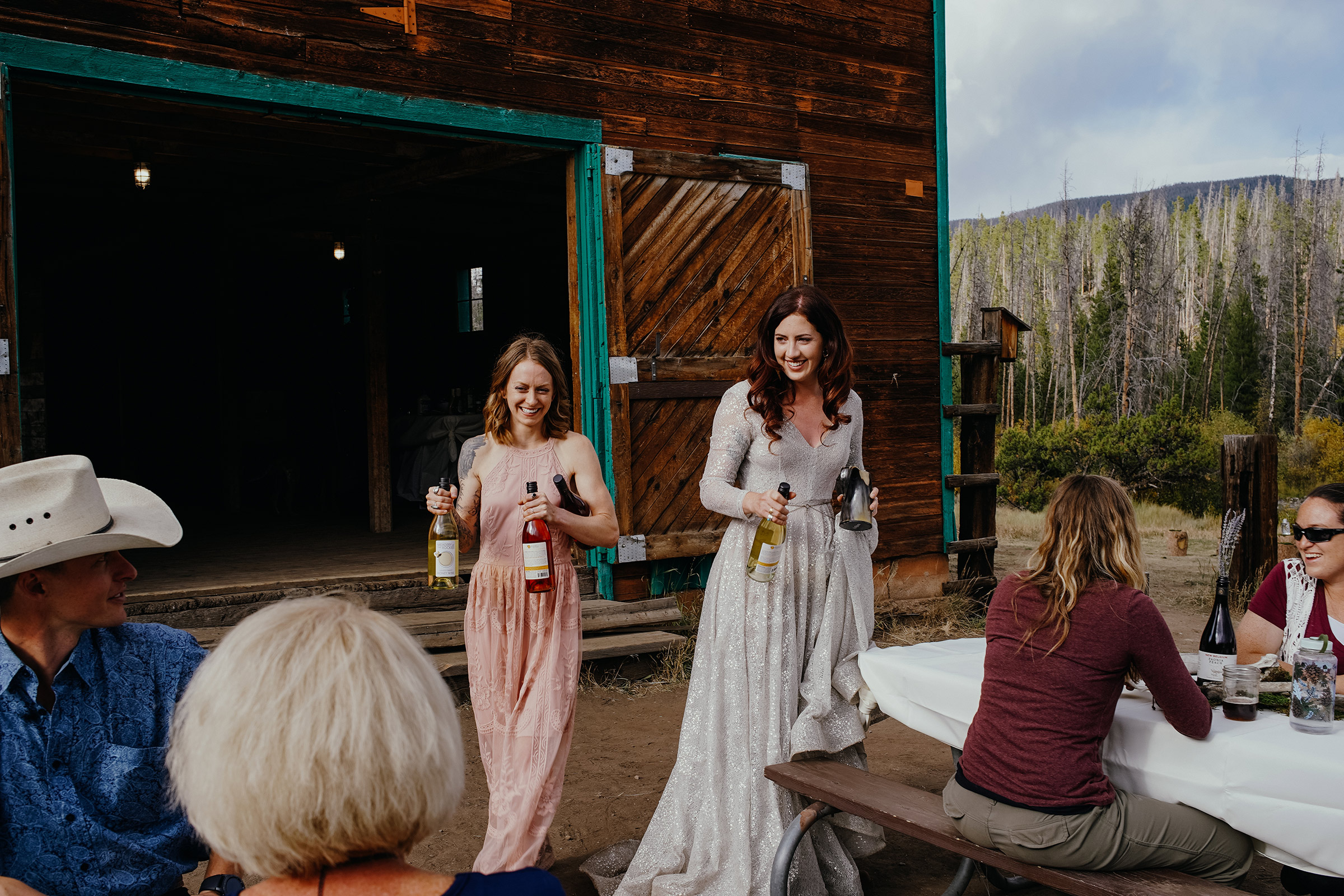 bride-and-bridesmaid-holding-wine-double-a-barn-grand-lake-colorado-raelyn-ramey-photography-595.jpg