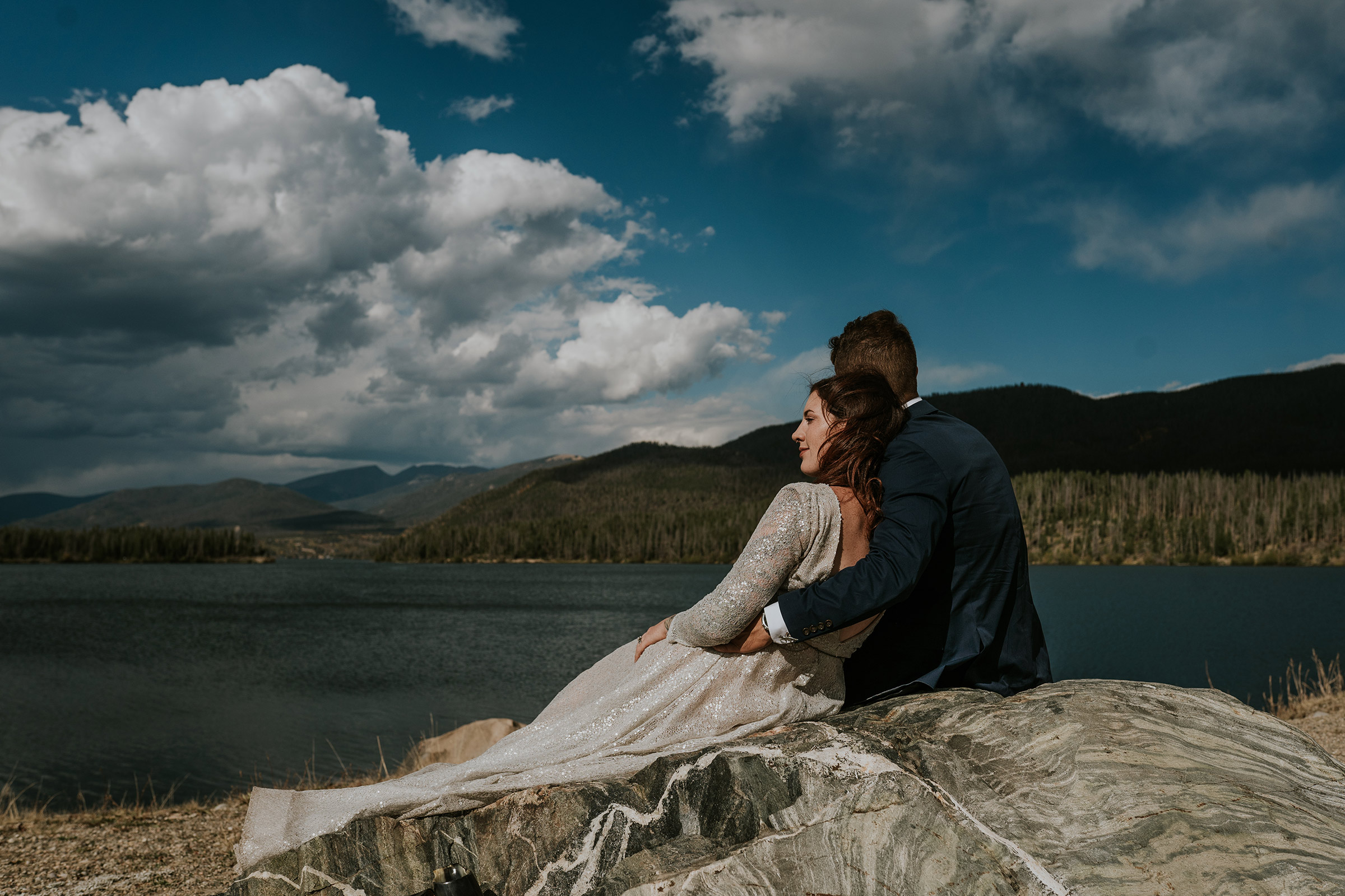 bride-groom-sitting-on-rock-looking-at-lake-double-a-barn-grand-lake-colorado-raelyn-ramey-photography-483.jpg