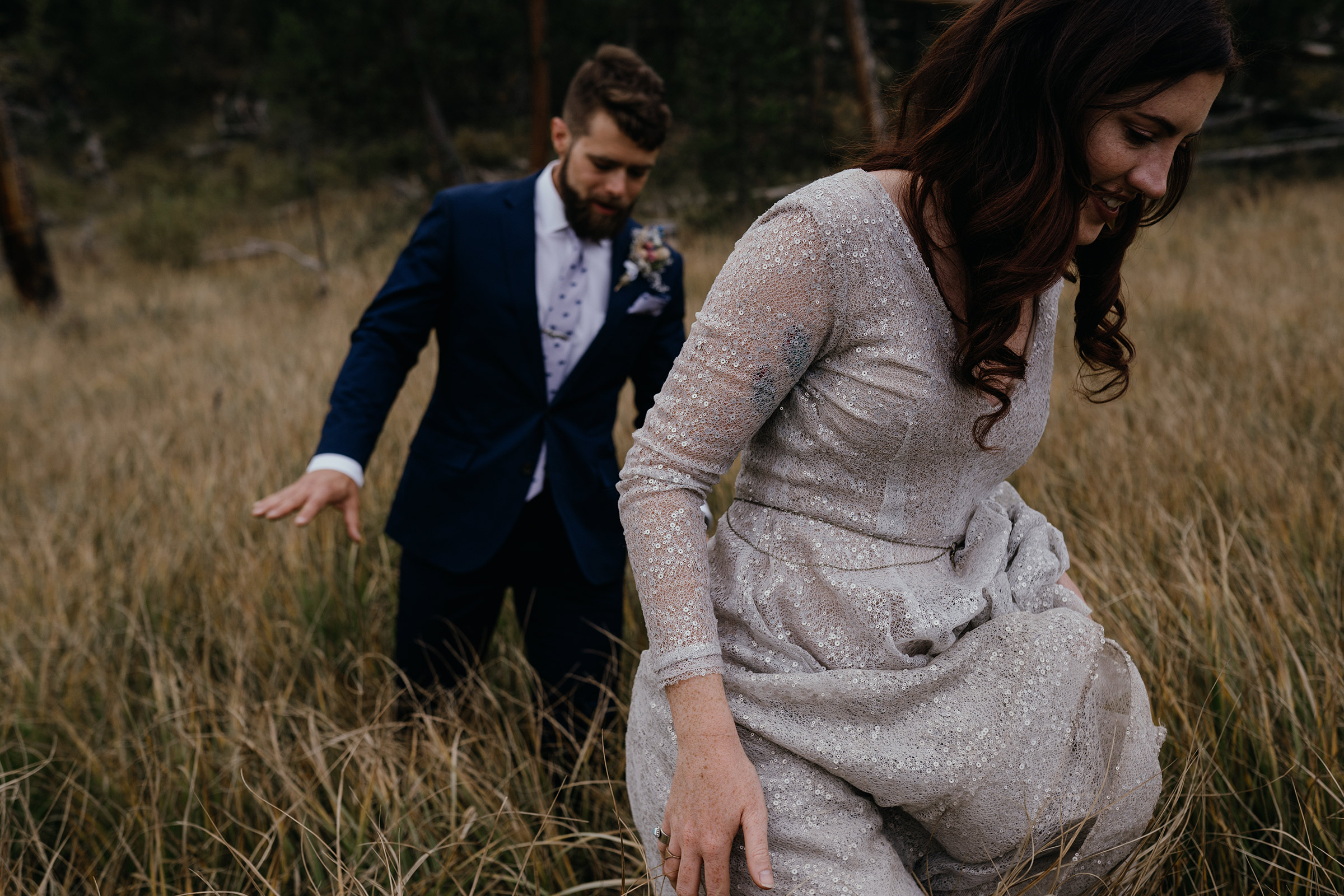 bride-groom-walking-in-tall-grass-double-a-barn-grand-lake-colorado-raelyn-ramey-photography-369.jpg