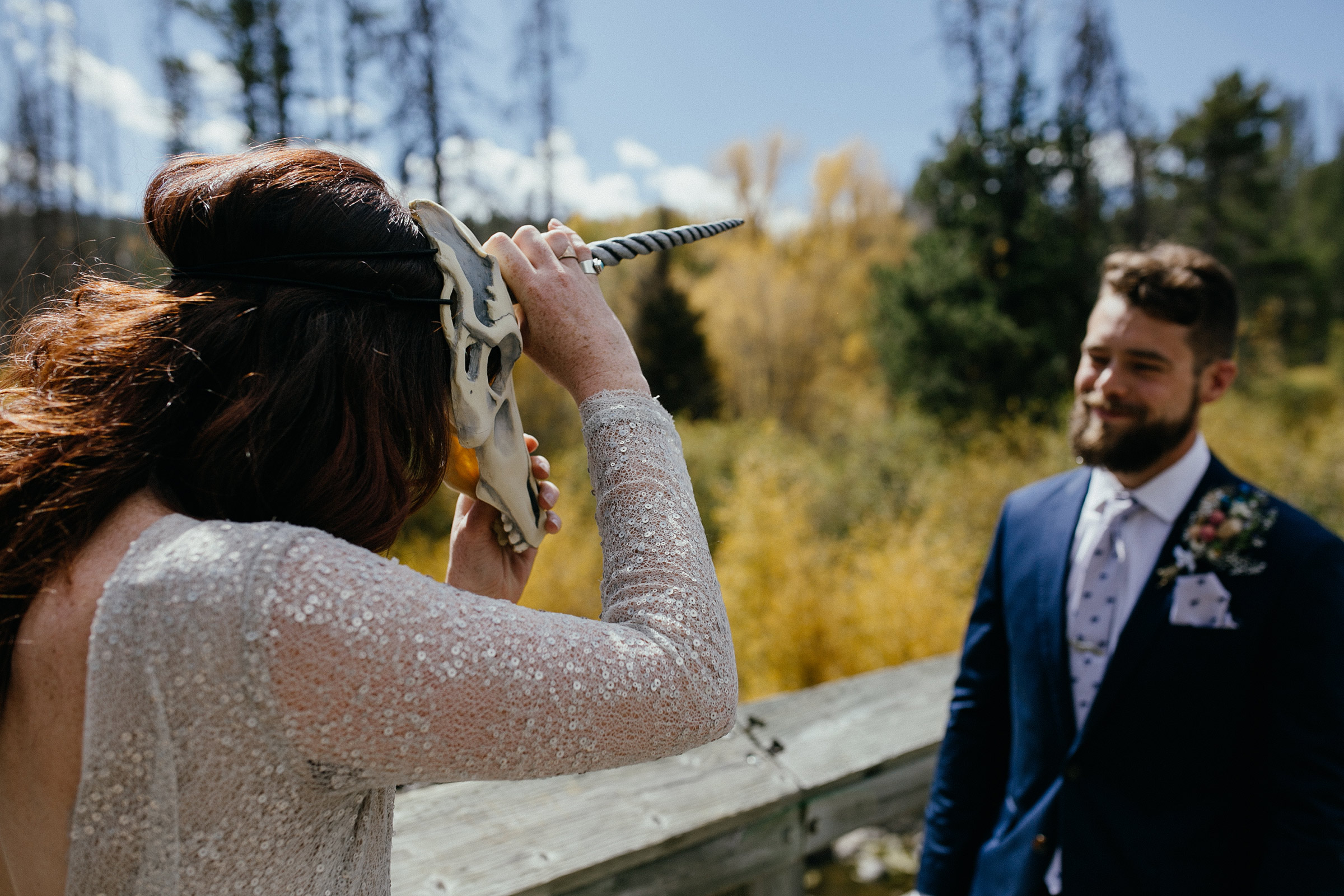 bride-taking-off-unicorn-mask-during-first-look-double-a-barn-grand-lake-colorado-raelyn-ramey-photography-224.jpg