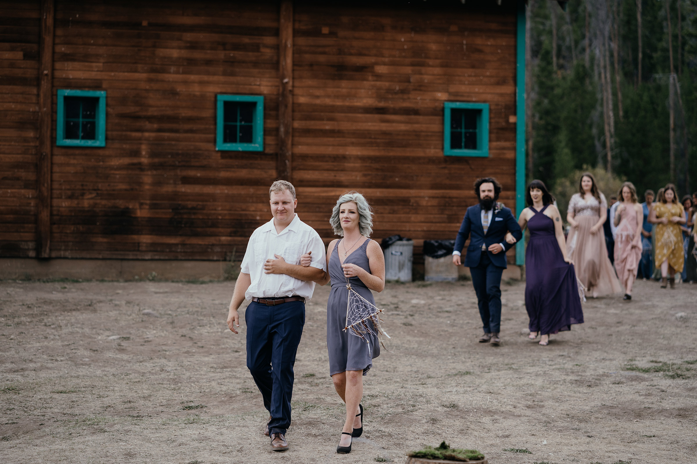 bridesmaids-groomsmen-walking-down-wedding-aisle-double-a-barn-grand-lake-colorado-raelyn-ramey-photography-407.jpg