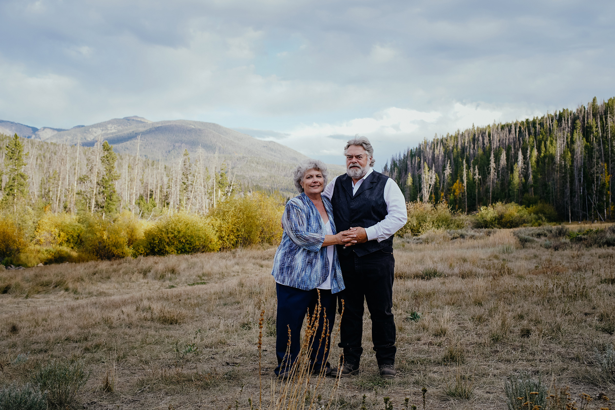 groom-parents-standing-in-front-of-mountains-double-a-barn-grand-lake-colorado-raelyn-ramey-photography-667.jpg