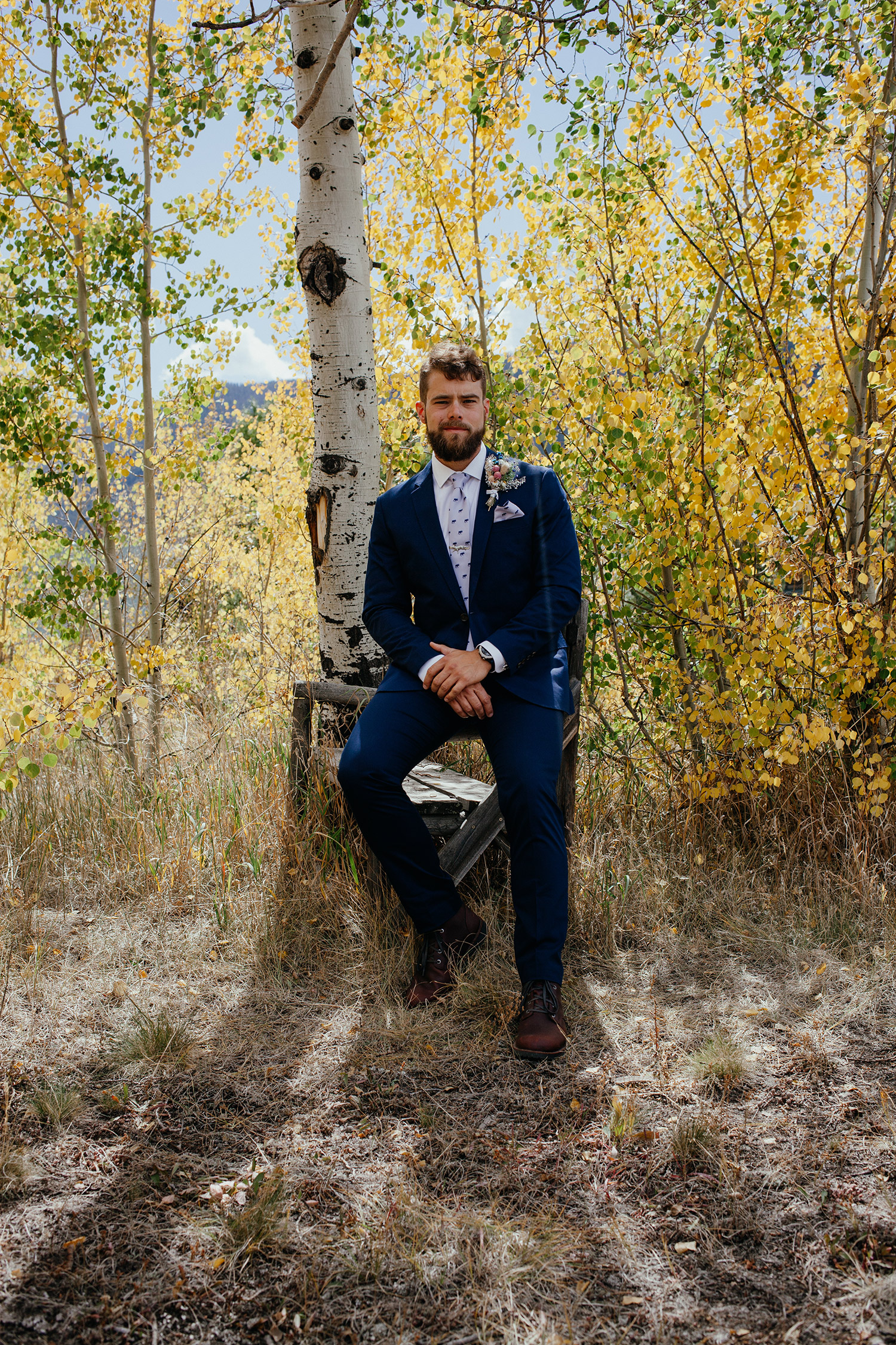 groom-sitting-on-tree-stump-double-a-barn-grand-lake-colorado-raelyn-ramey-photography-155.jpg
