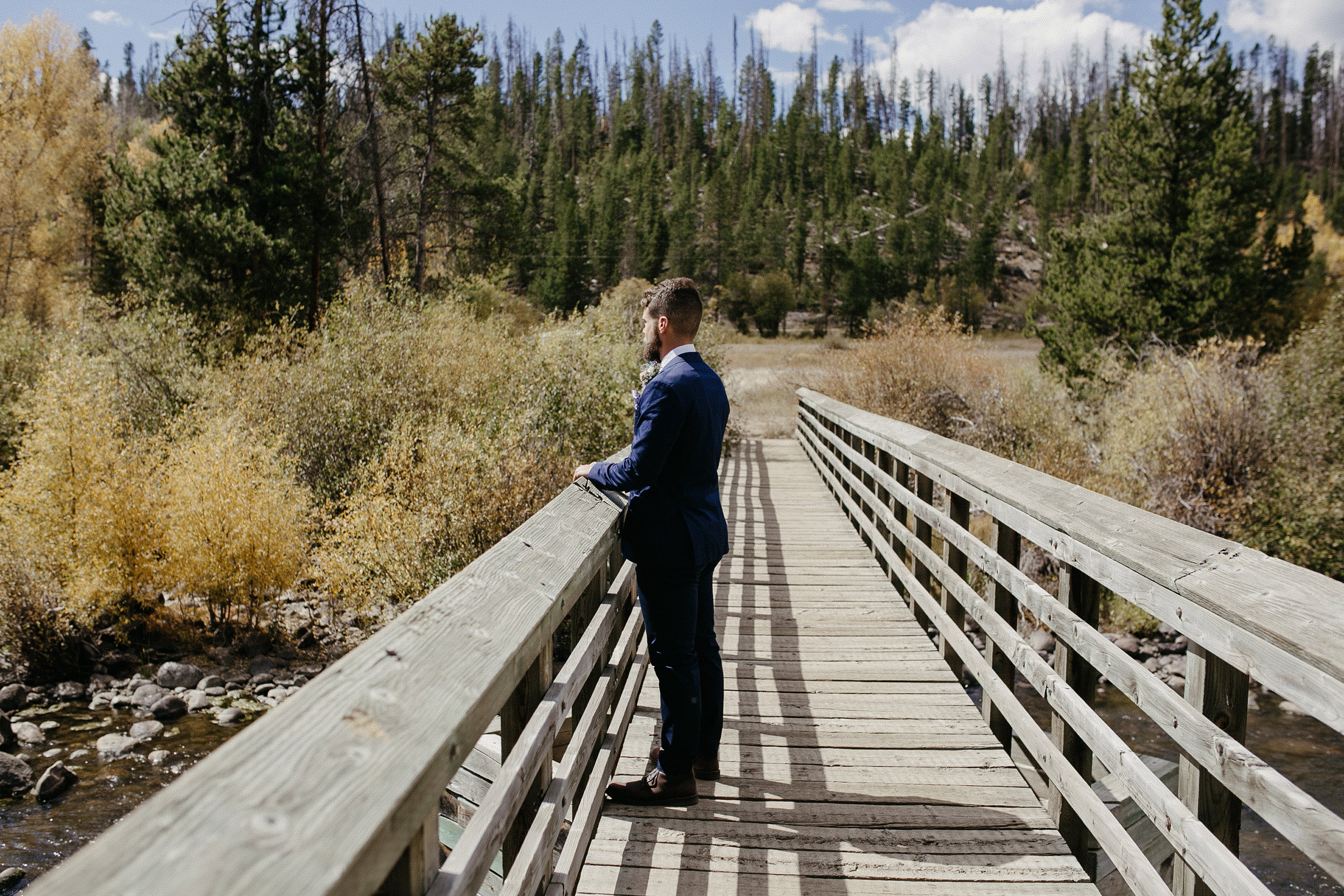 groom-waiting-on-bridge-for-first-look-double-a-barn-grand-lake-colorado-raelyn-ramey-photography-216.jpg