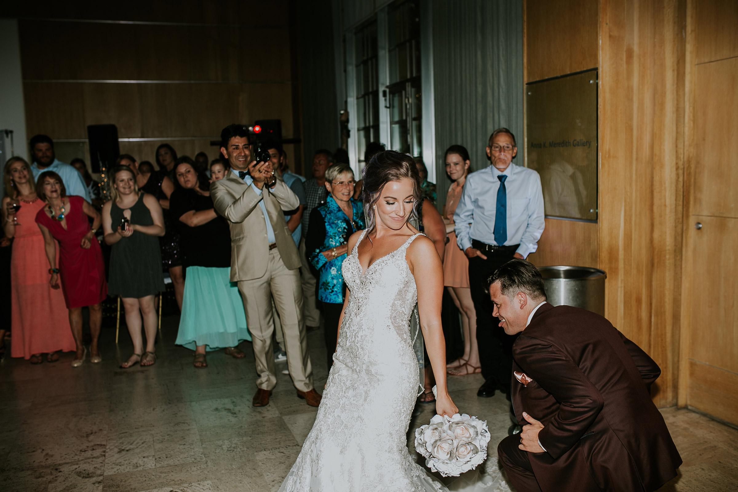 bride-and-groom-enterance-dancing-around-desmoines-iowa-art-center-raelyn-ramey-photography.jpg