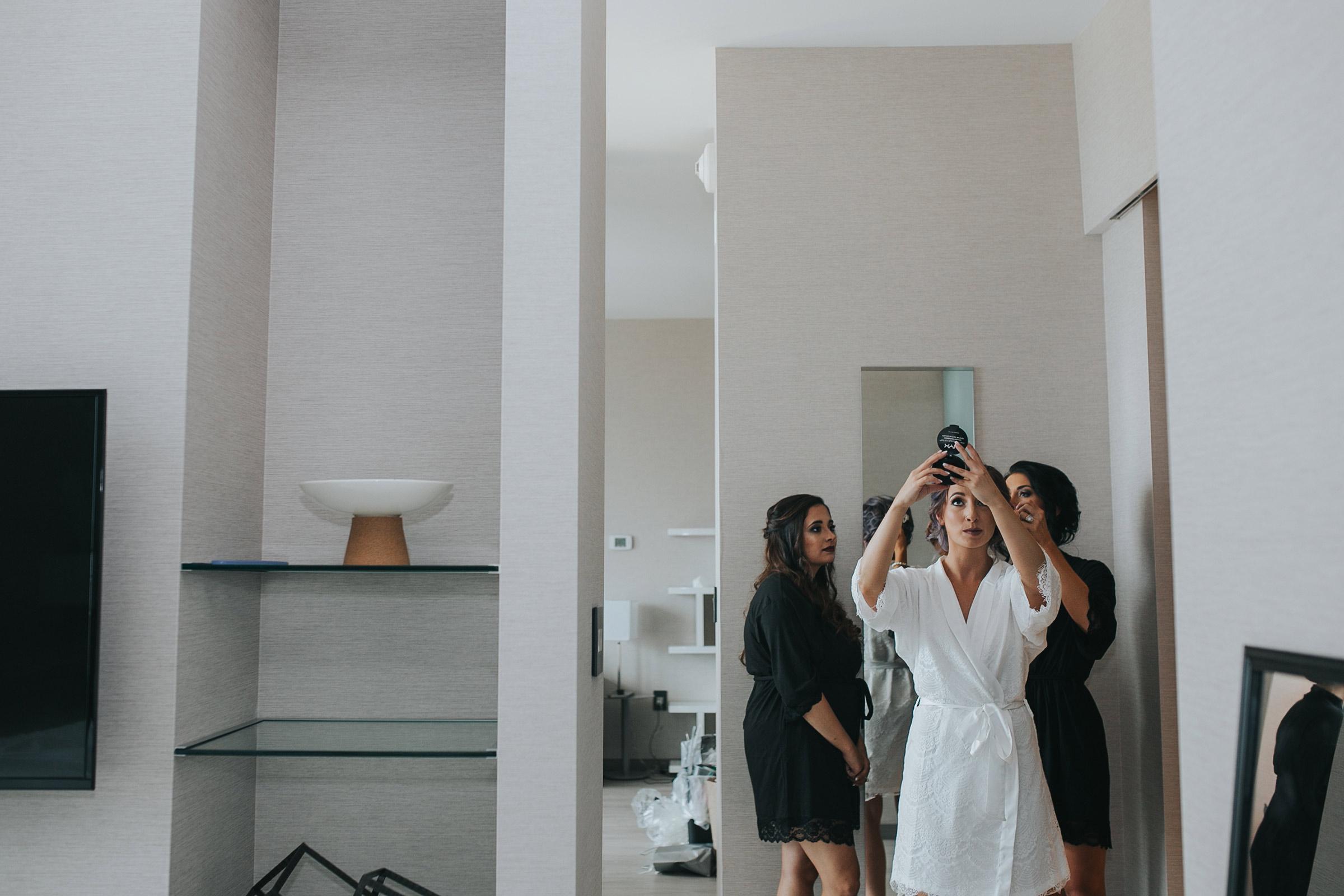 bride-checking-hair-in-mirror-desmoines-iowa-ac-hotel-raelyn-ramey-photography.jpg