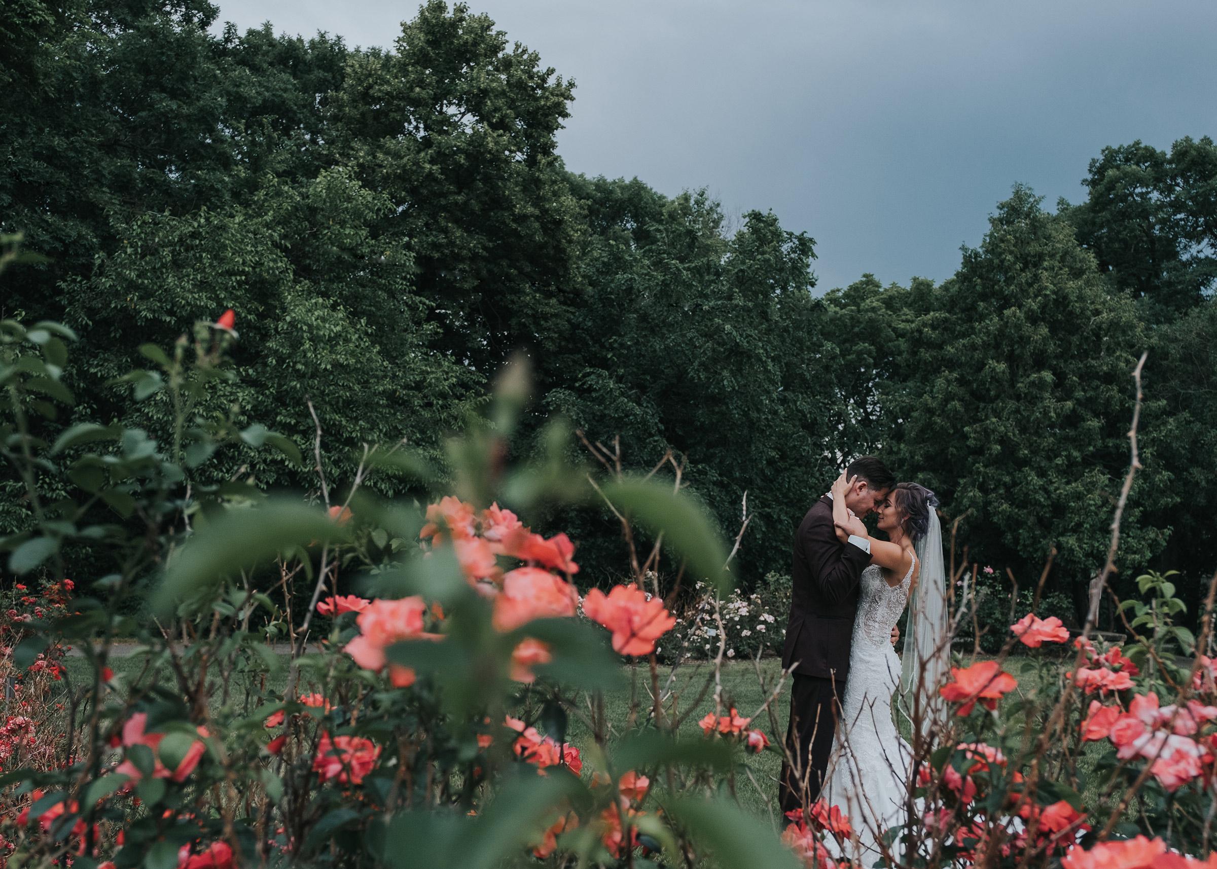 bride-groom-getting-close-in-rose-garden-desmoines-iowa-art-center-raelyn-ramey-photography.jpg